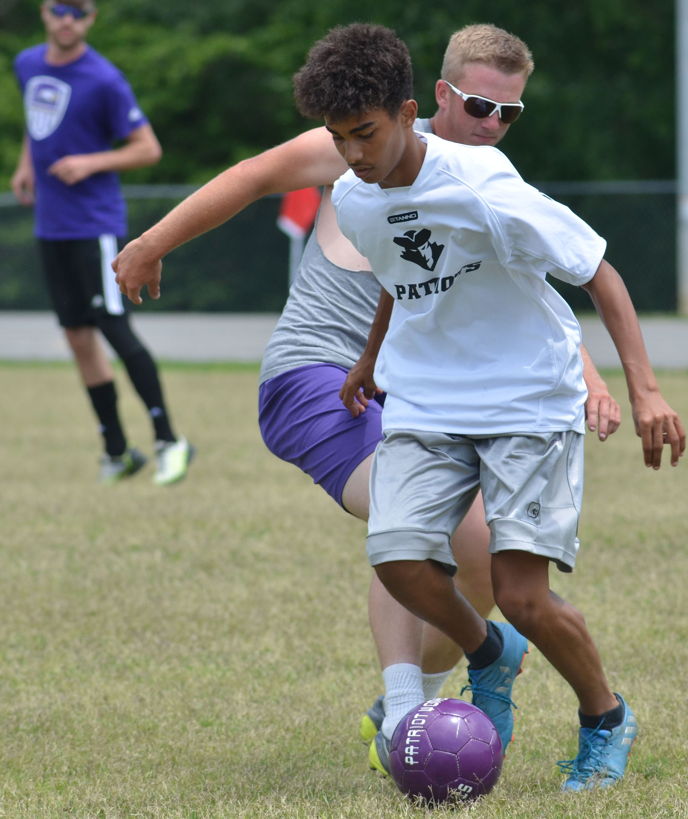 CHS sophomore David Silva runs as alumni player Logan Dial tries to steal the ball.