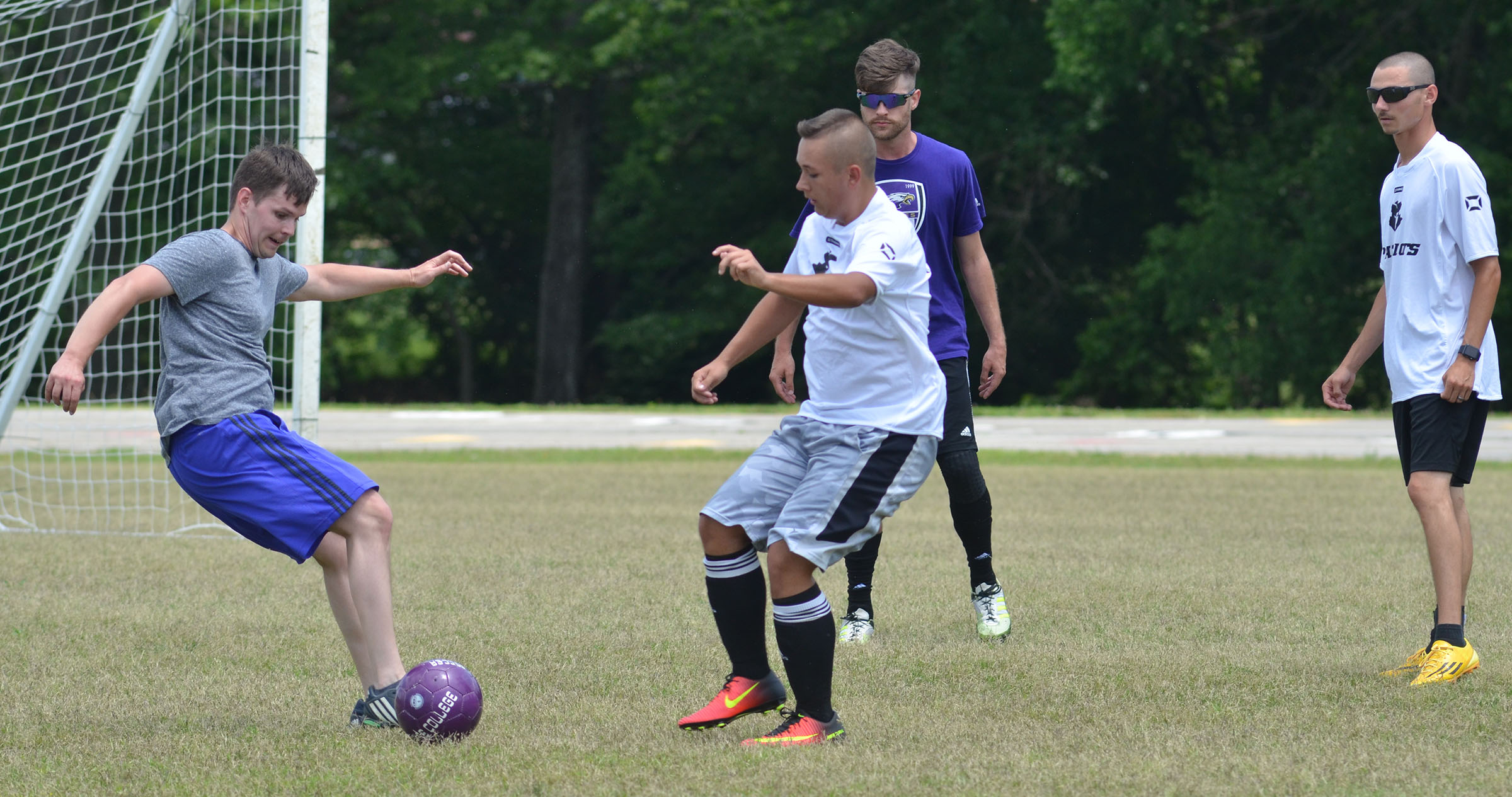 CHS soccer alumni player Jeff Muncie, at left, battles senior Cody Davis for the ball.