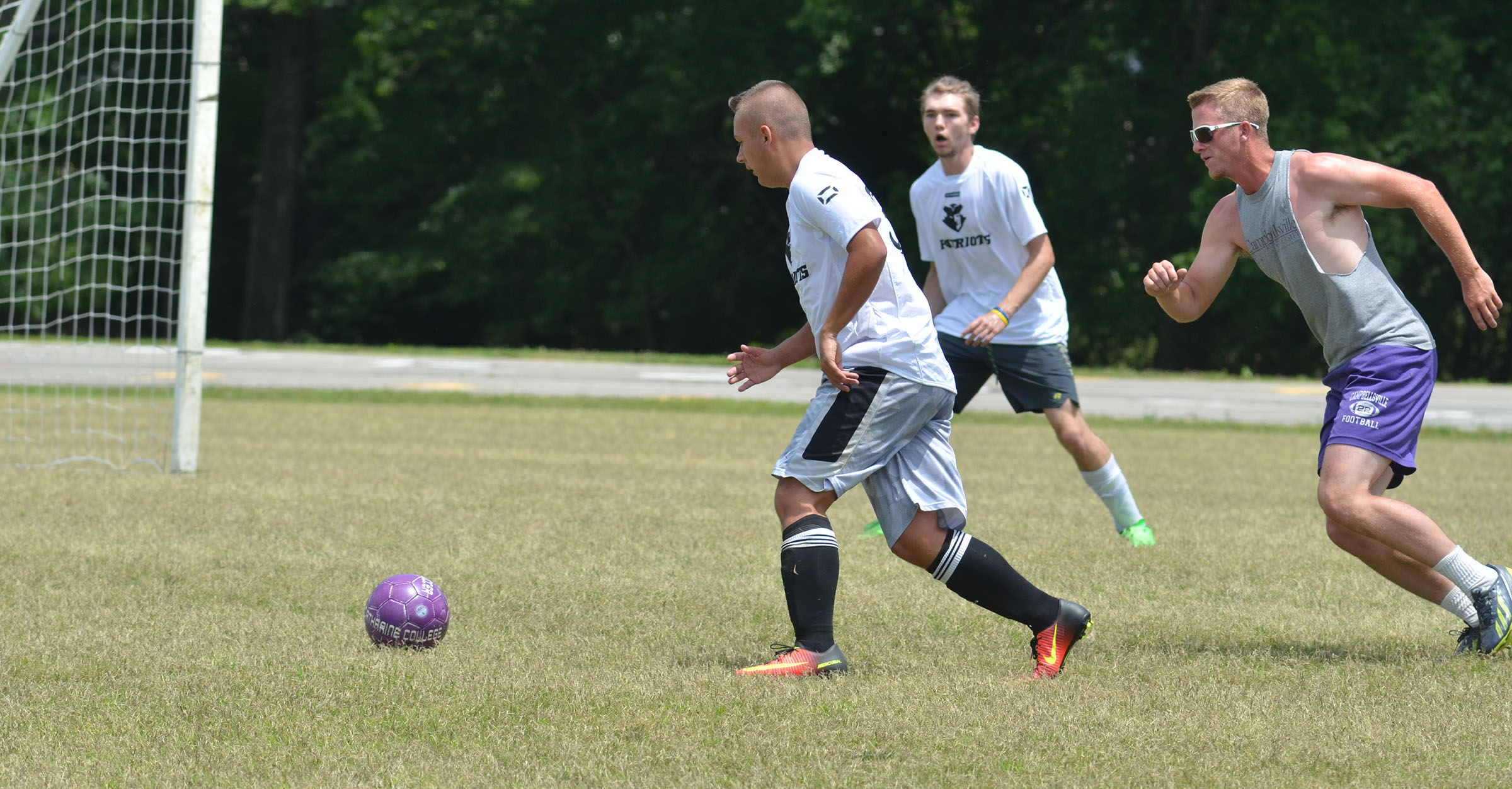 CHS senior Cody Davis kicks the ball toward the goal, with alumni player Logan Dial right behind him.