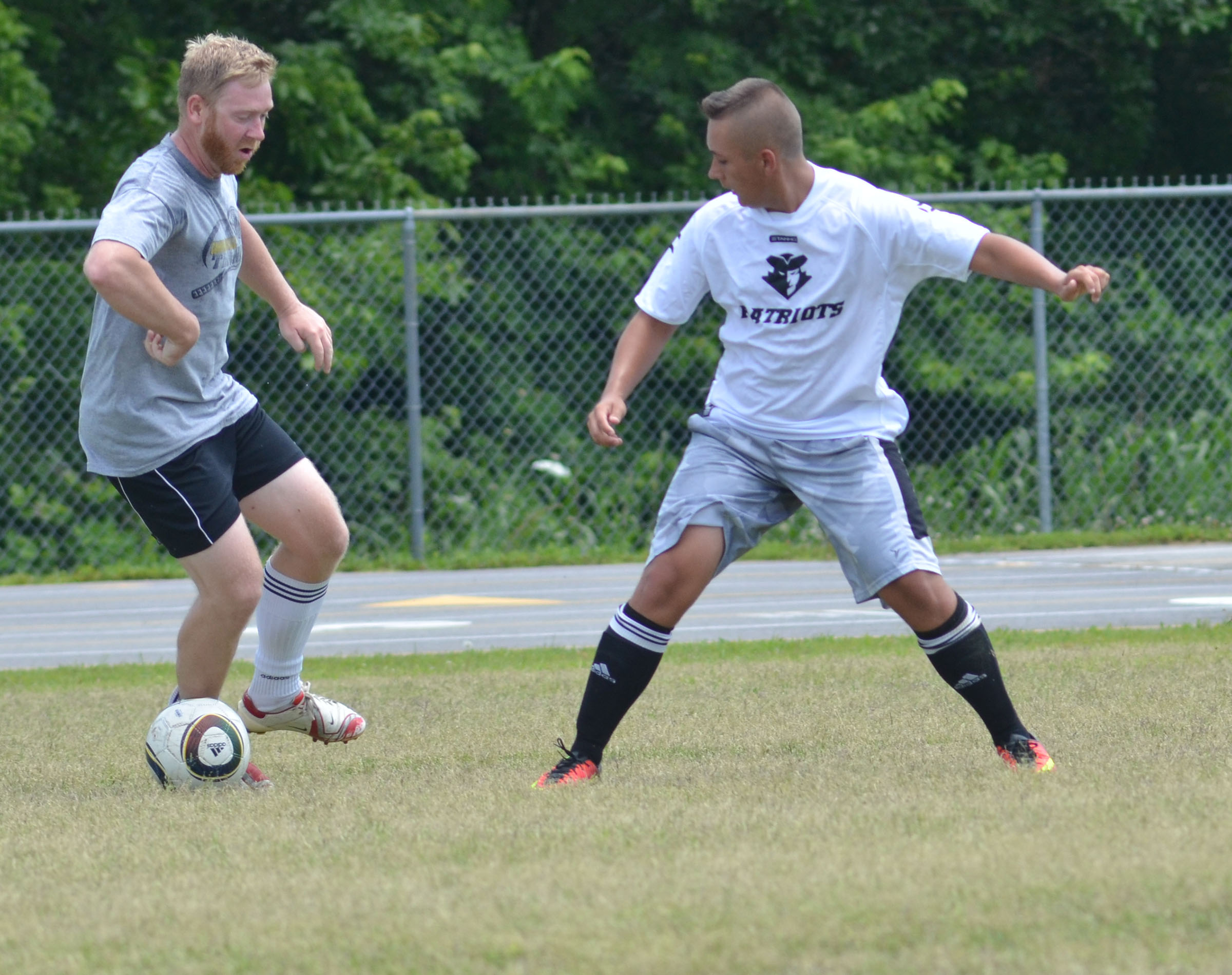 CHS soccer alumni player Luke Lawless, at left, battles senior Cody Davis.