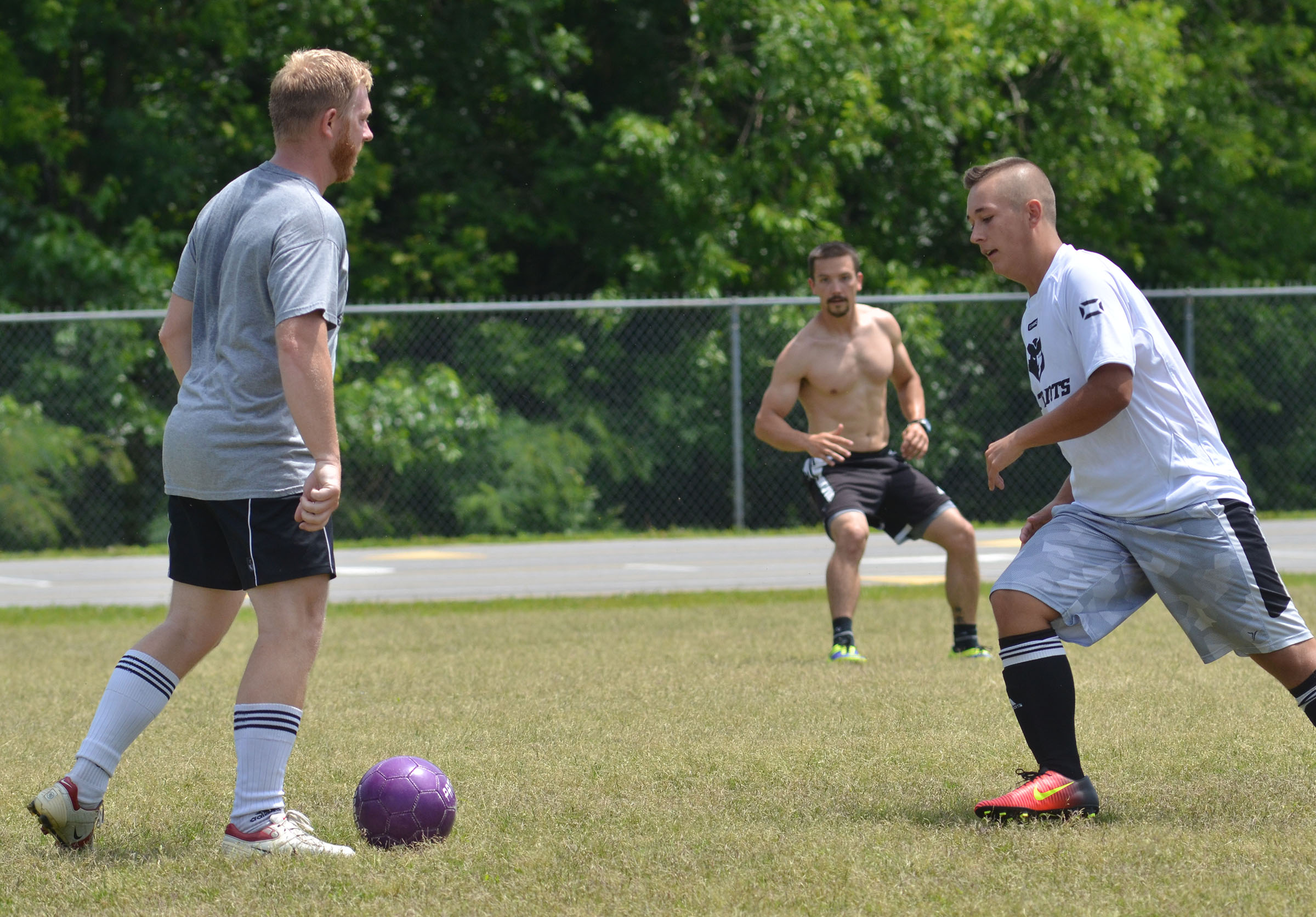 CHS soccer alumni player Luke Lawless gets set to kick the ball as senior Cody Davis plays defense.