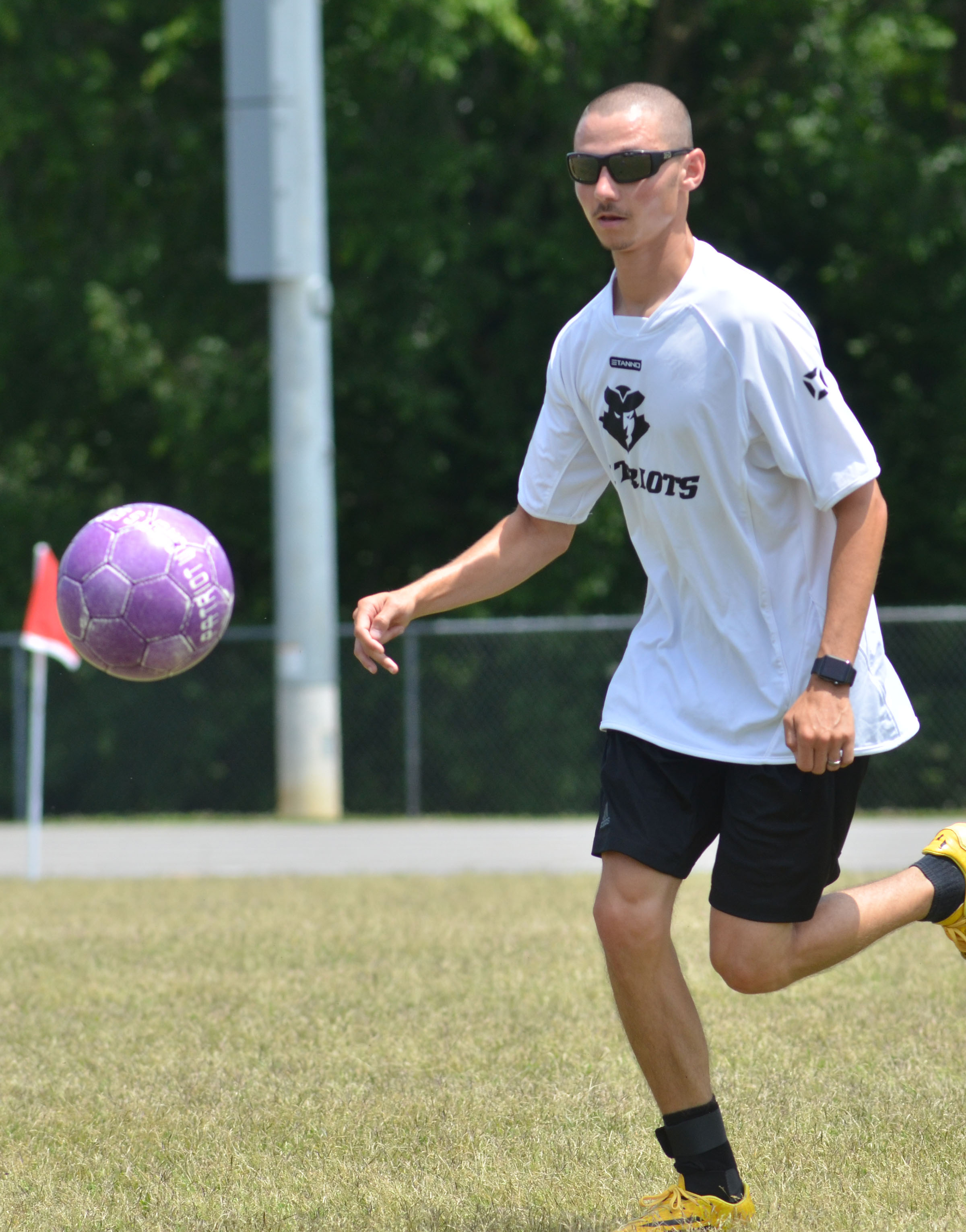 CHS soccer alumni player Bradley Harris, who is also head coach, kicks the ball.