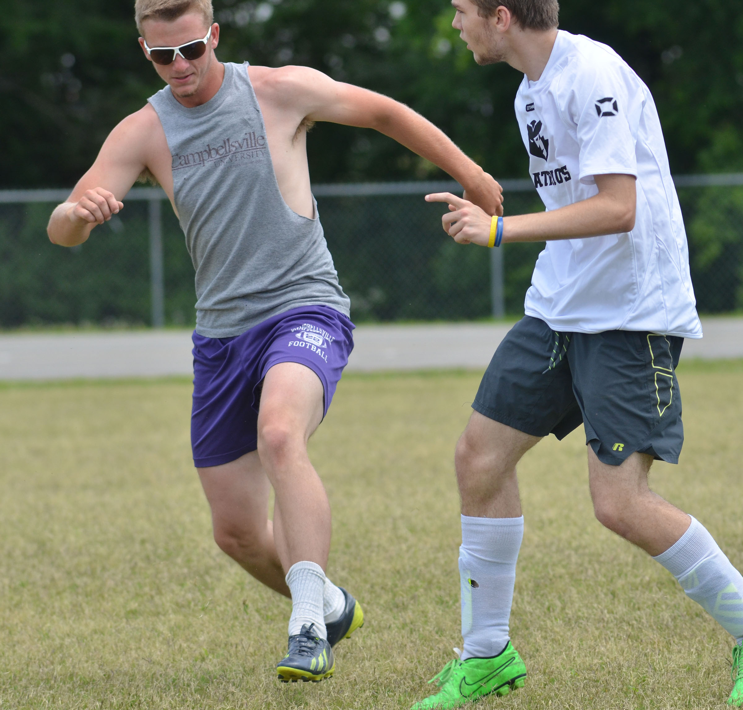CHS soccer alumni player Logan Dial, at left, and senior Christian Berry run for the ball.