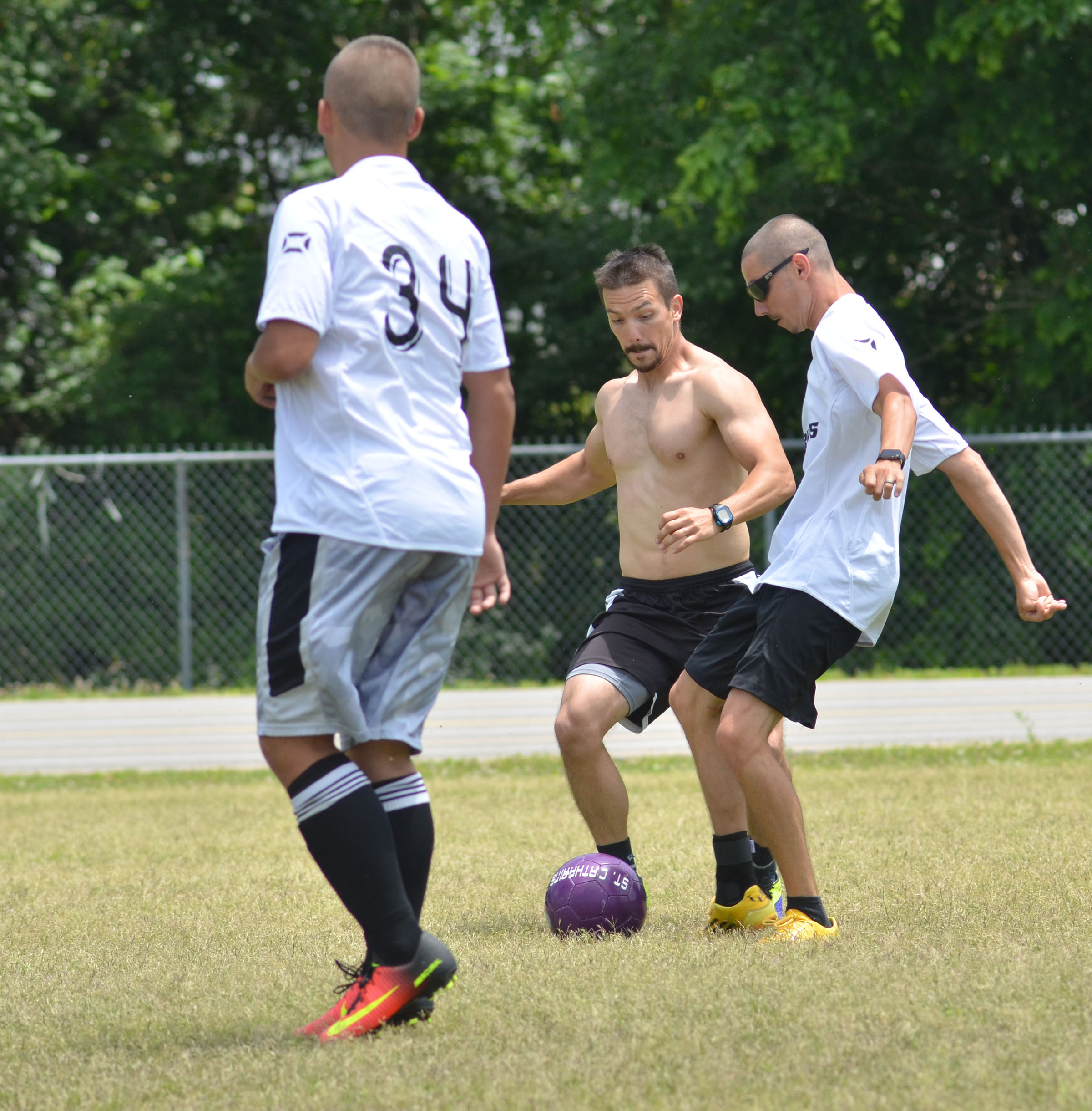 CHS soccer alumni player Drew Skaggs, center, battles Bradley Harris, an alumni player and head coach, for the ball.