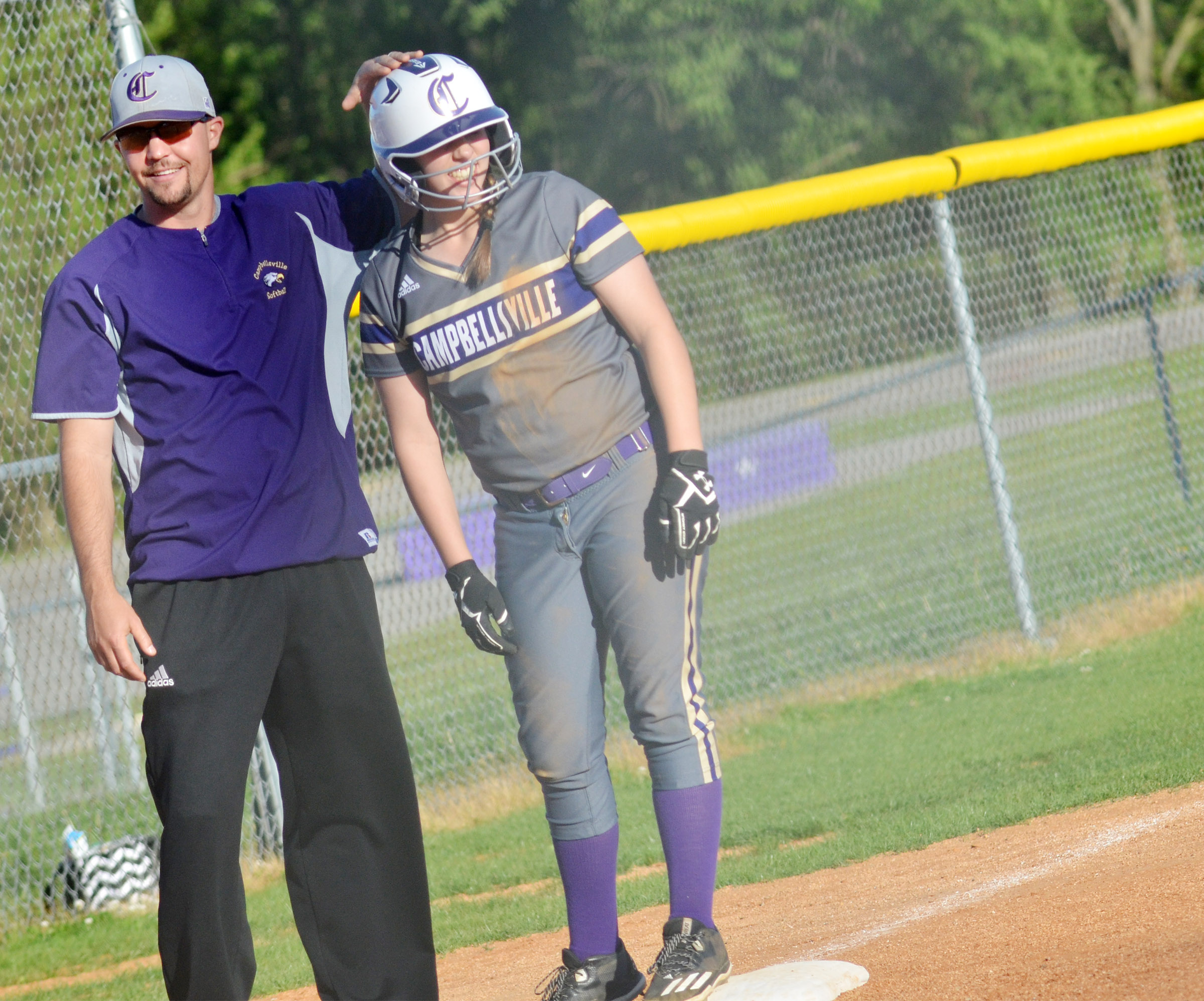 CHS head softball coach Weston Jones congratulates Campbellsville Middle School eighth-grader Abi Wiedewitsch after she makes it safely back to third base.