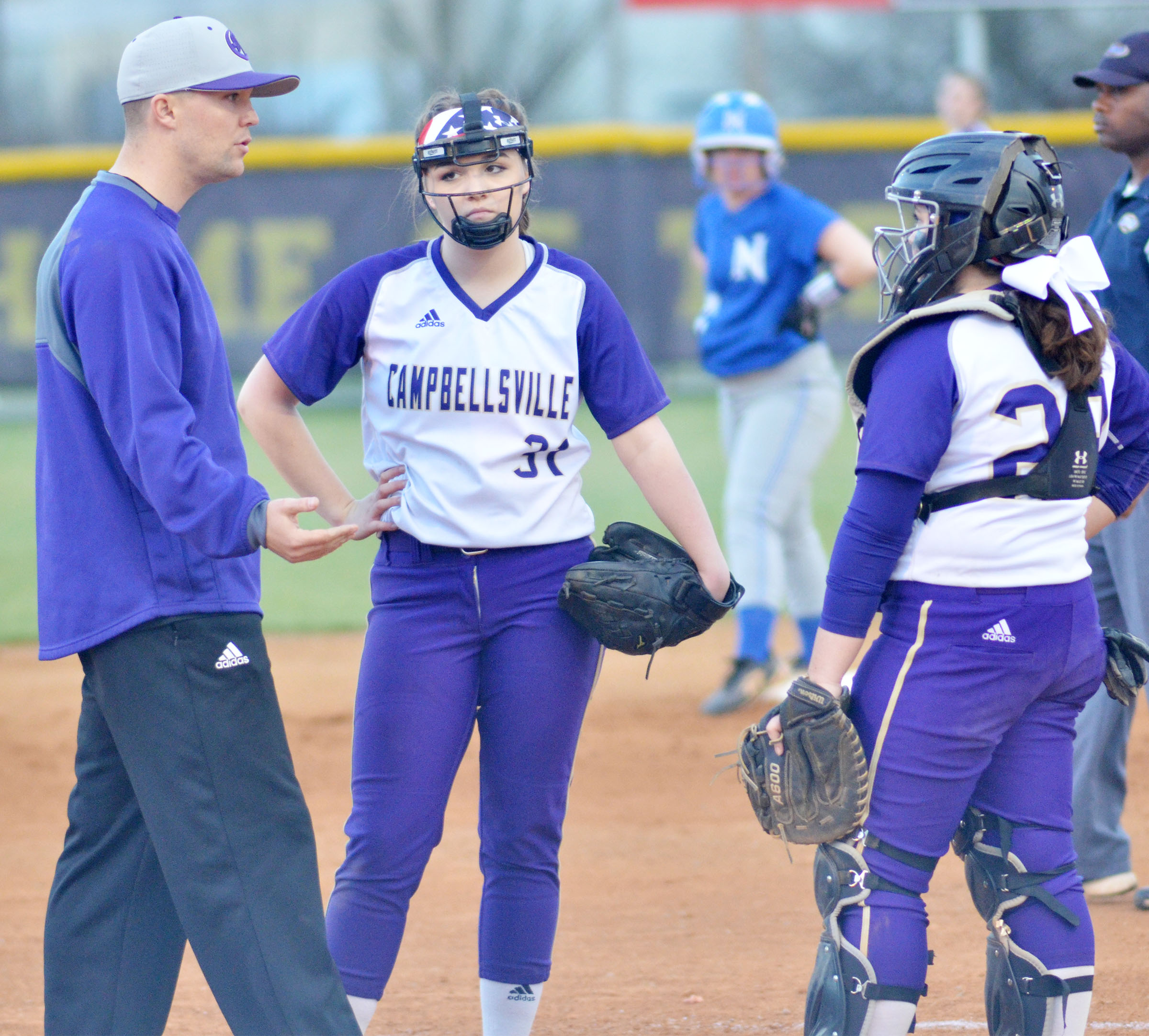 CHS head softball coach Weston Jones meets with Campbellsville Middle School eighth-grader Kenzi Forbis, who pitches for the Lady Eagles, and catcher Caitlin Bright, a junior.