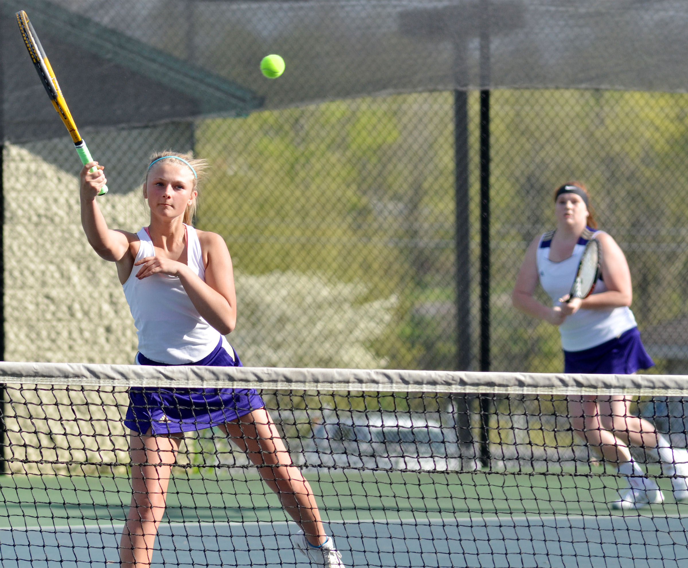 CHS freshman Victoria Cox, at left, hits the ball as doubles partner Mallory Haley, a senior, looks on.