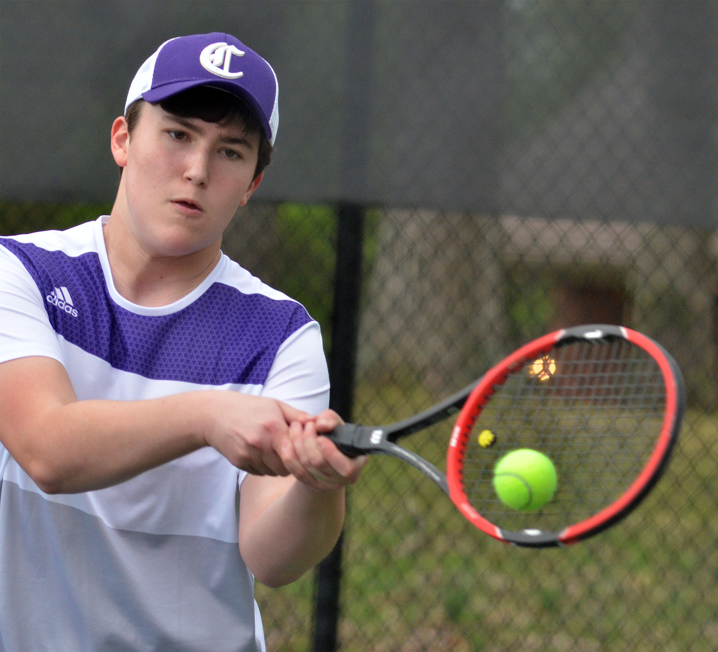 CHS senior Zack Settle returns a serve.