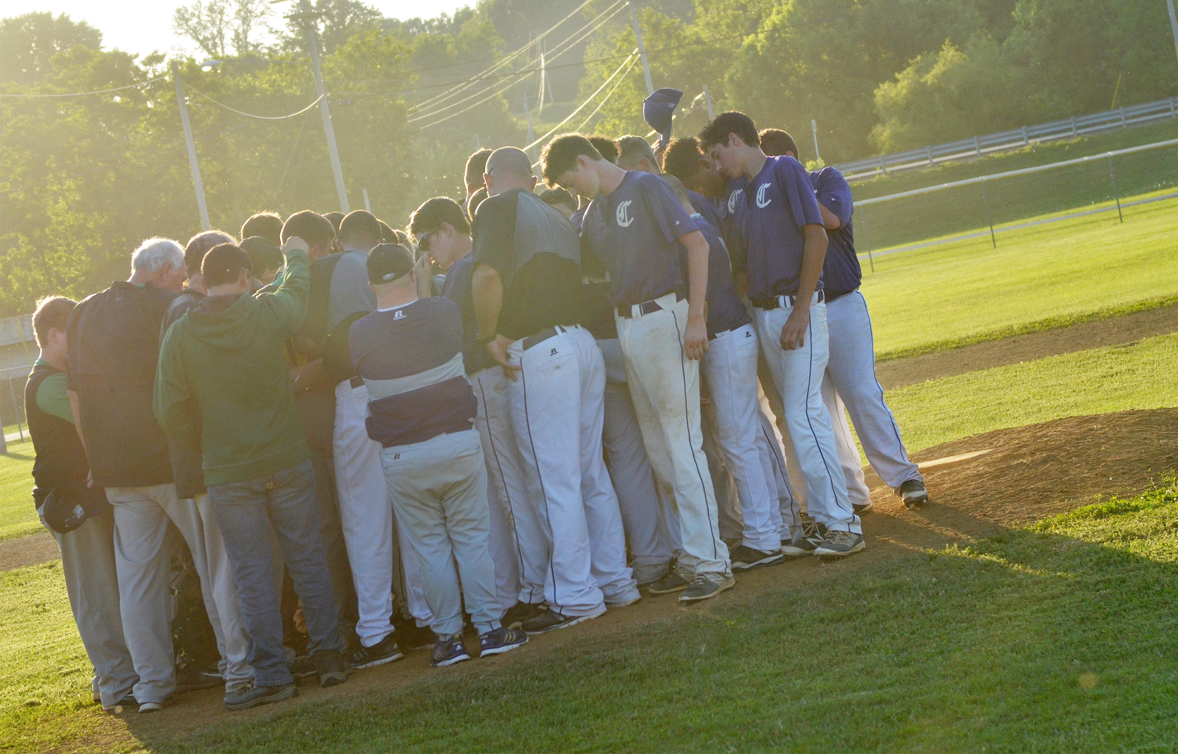 CMS baseball team prays with Green County after the game.