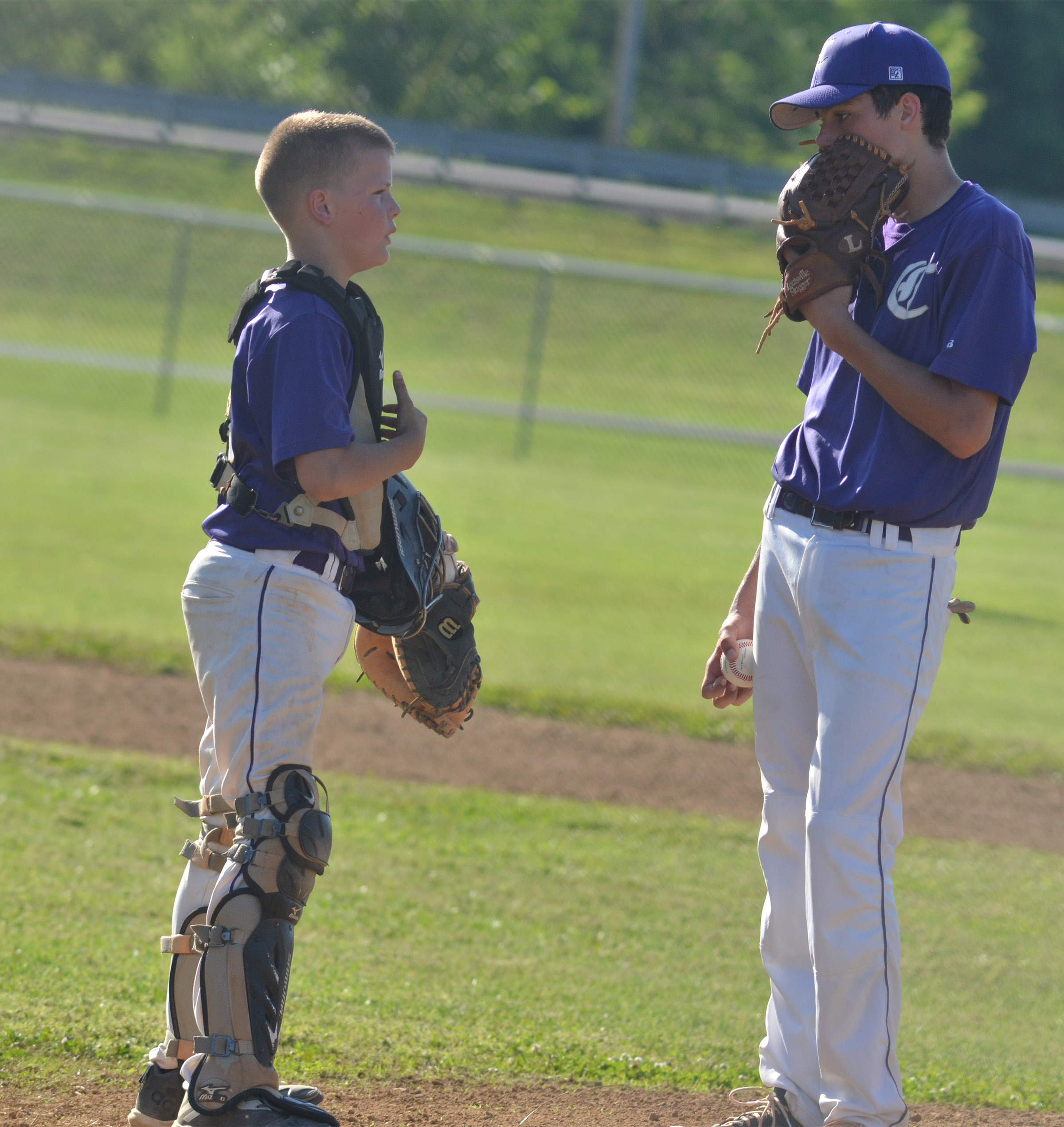 CMS sixth-grader Konner Forbis talks to eighth-grader Kameron Smith as he gets set to pitch.