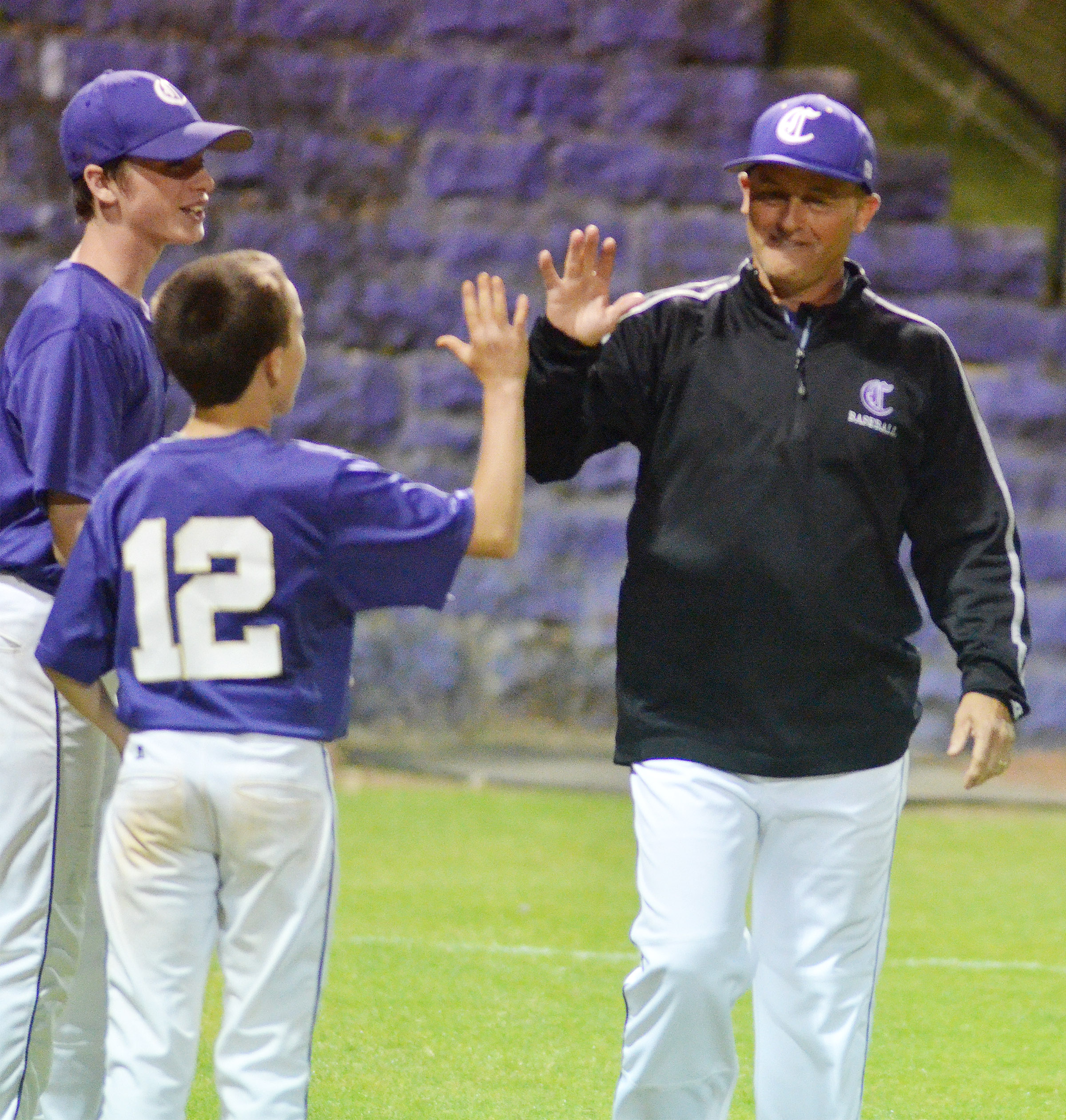 CMS head baseball coach Lynn Kearney high fives sixth-grader Chase Hord after the win.
