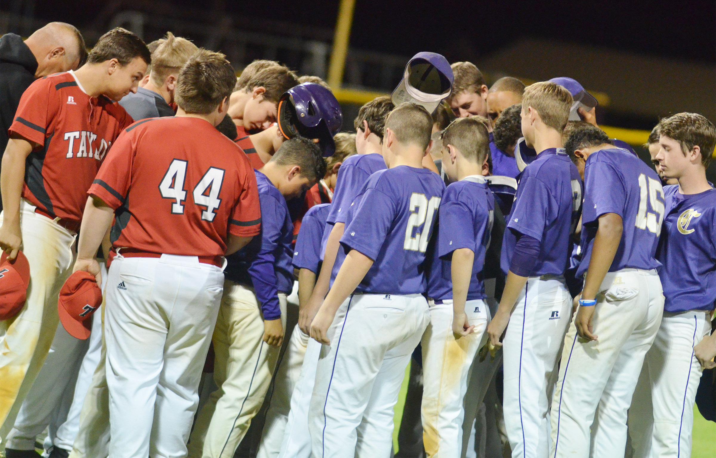CMS baseball players pray with the Taylor County team after the game.