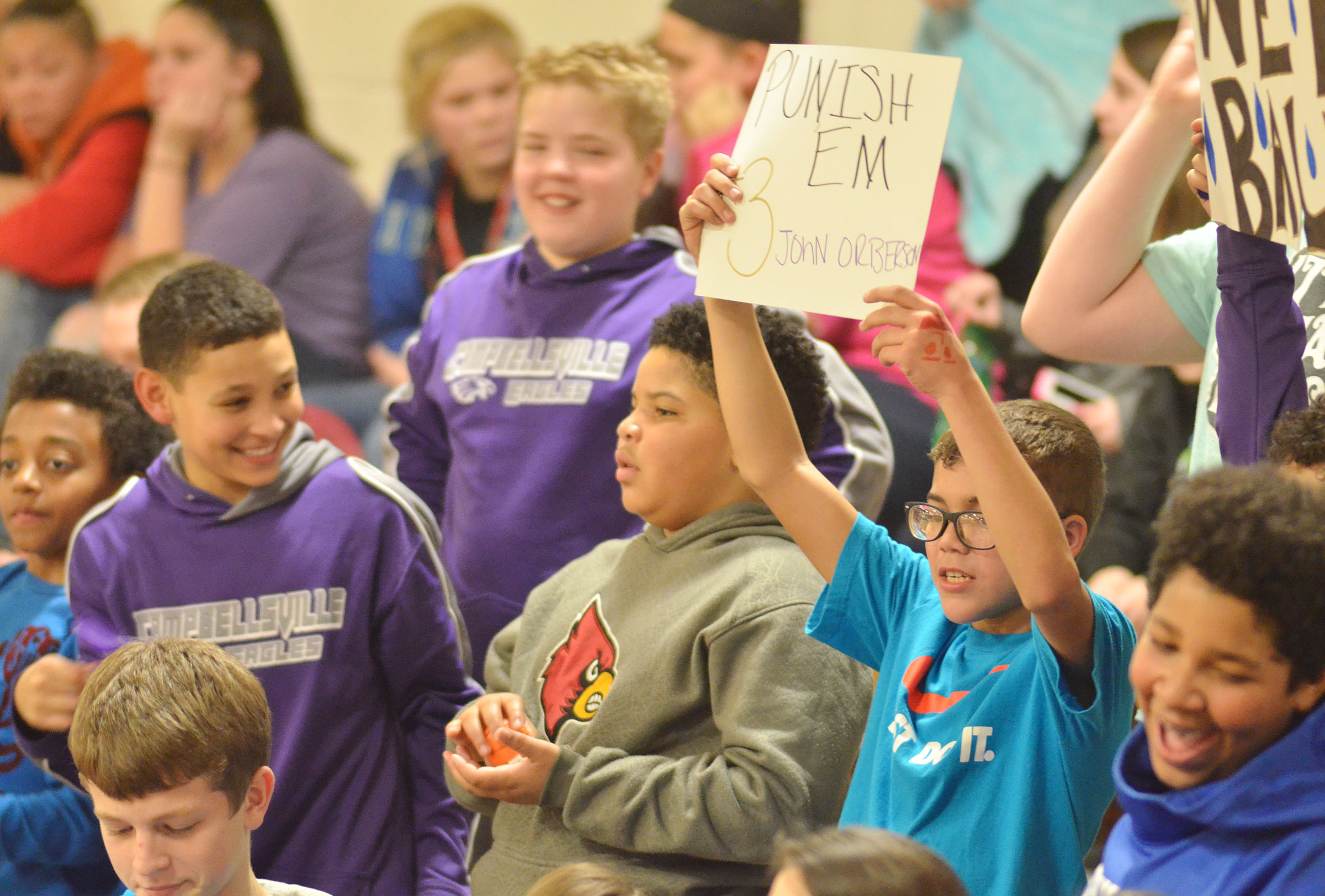 CMS seventh-grader Logan Phillips holds a sign for eighth-grade player John Orberson.
