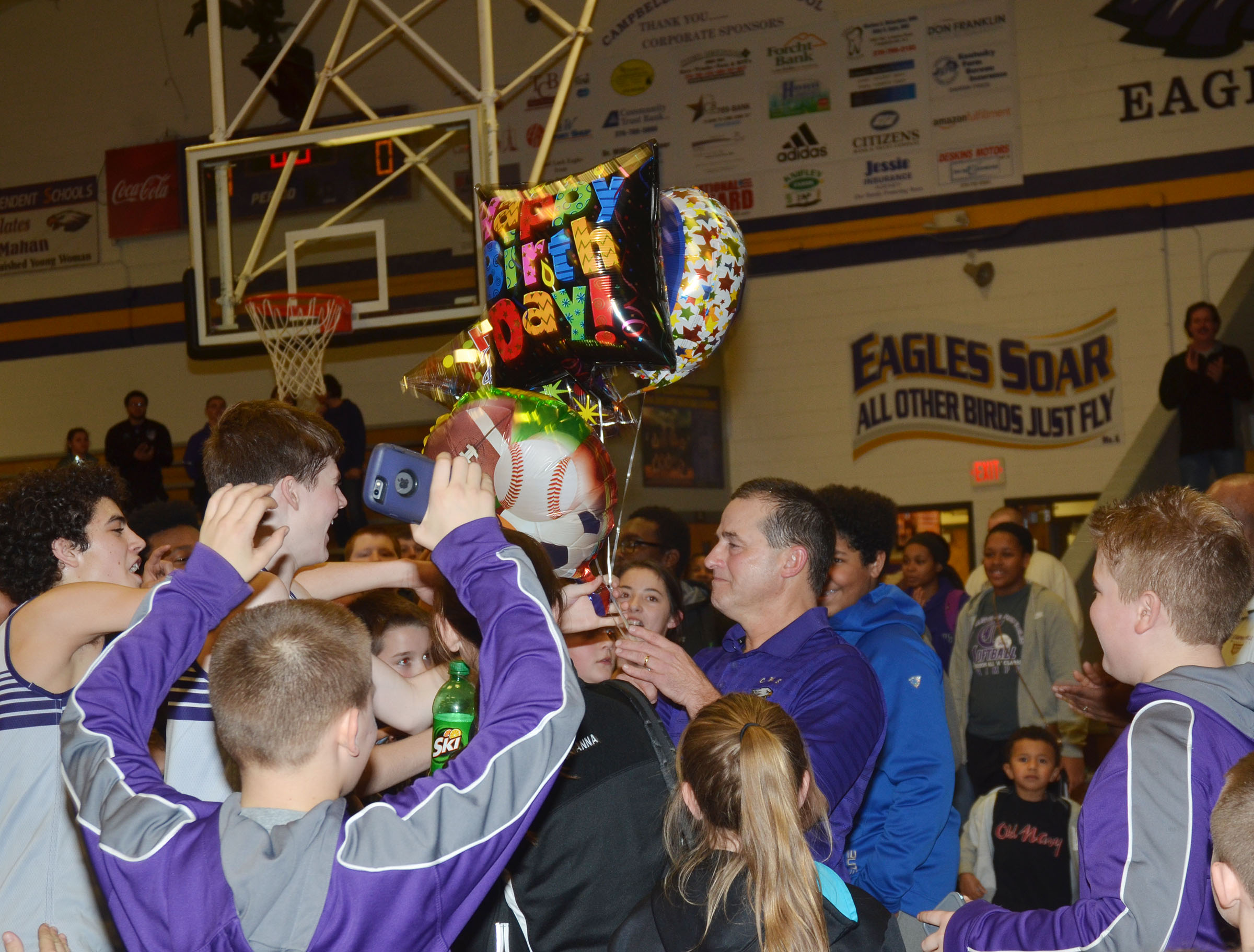 CMS boys' basketball coach Lynn Kearney receives balloons from his players in honor of his birthday, which was the same day as the championship game.