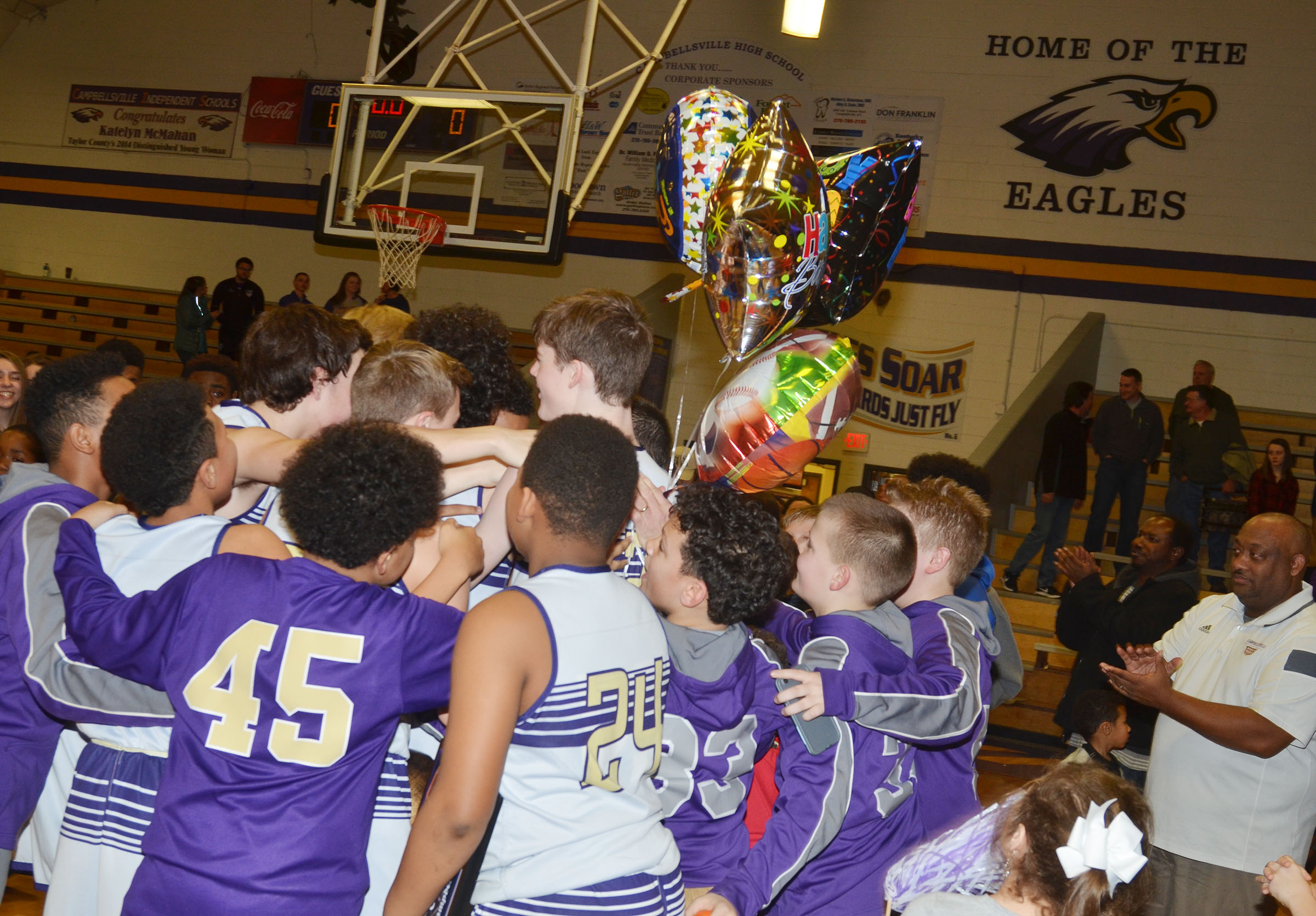 CMS boys' basketball players surround coach Lynn Kearney after he is named CKMSAC Coach of the Year.