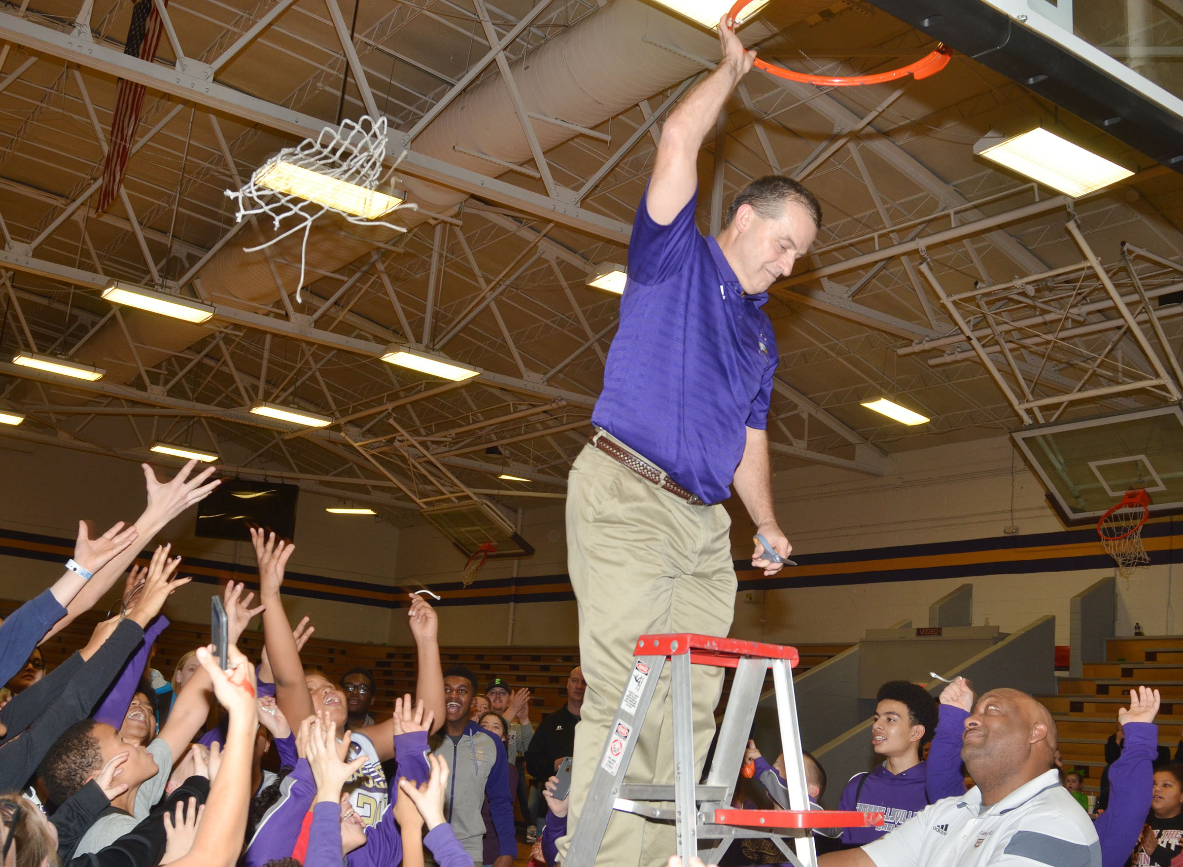 CMS boys' basketball coach Lynn Kearney throws the net after cutting it down.