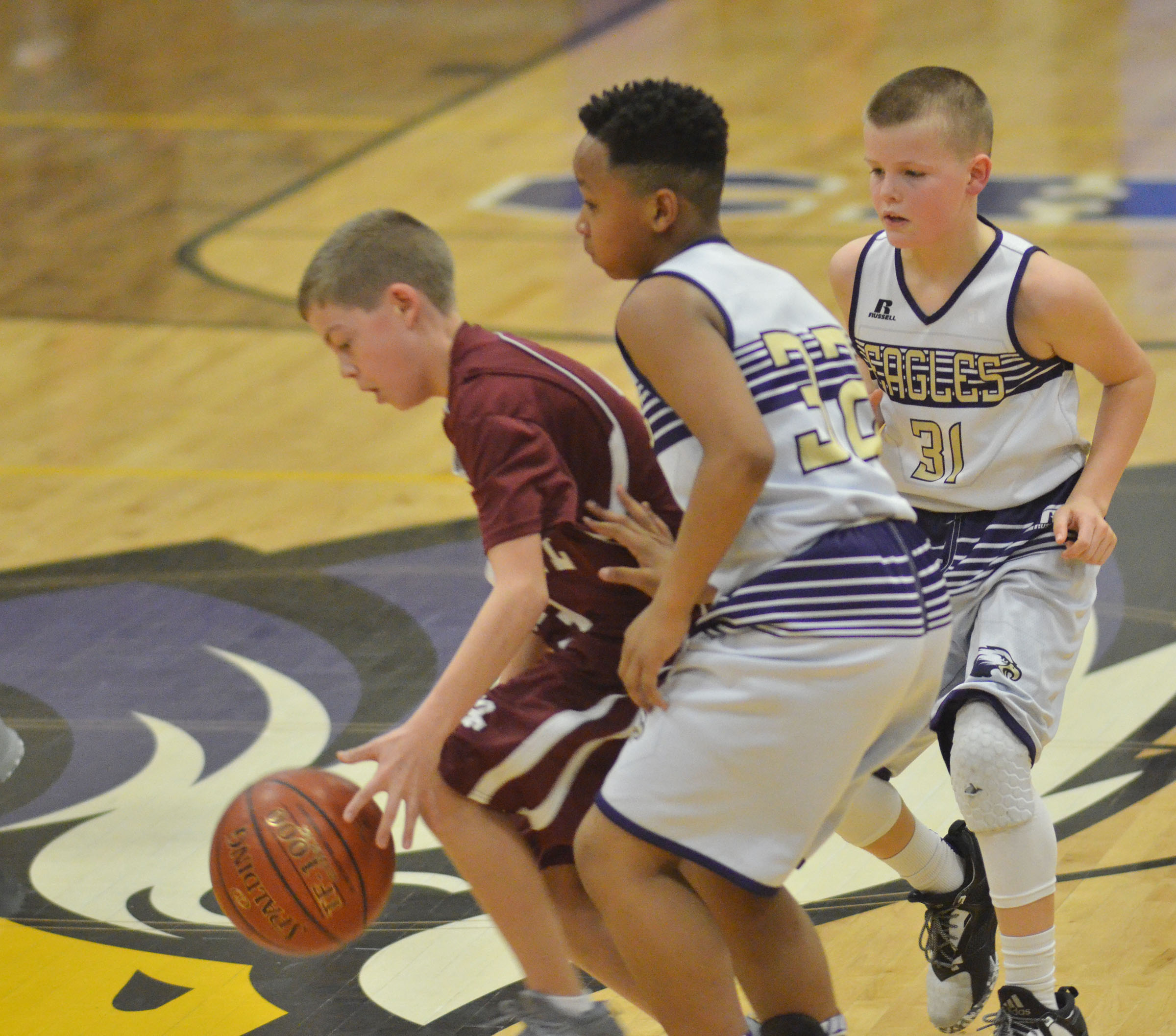 CMS sixth-graders Deondre Weathers, center, and Konner Forbis play defense.