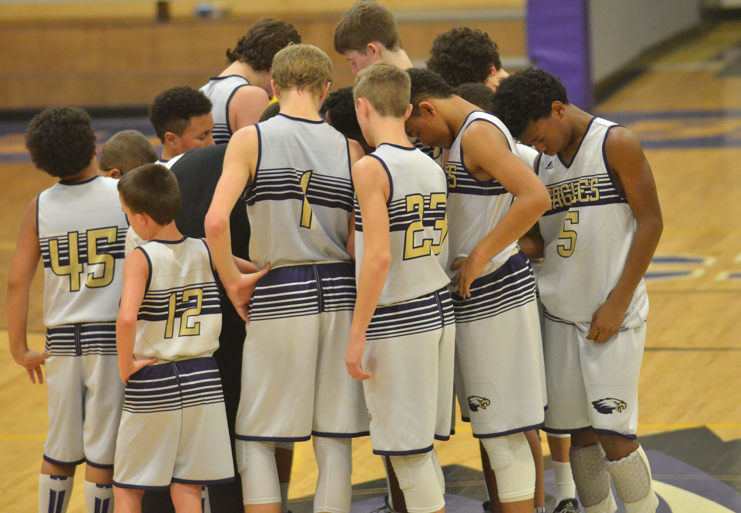 CMS boys' basketball players pray together after winning their last regular season game and finishing as undefeated.