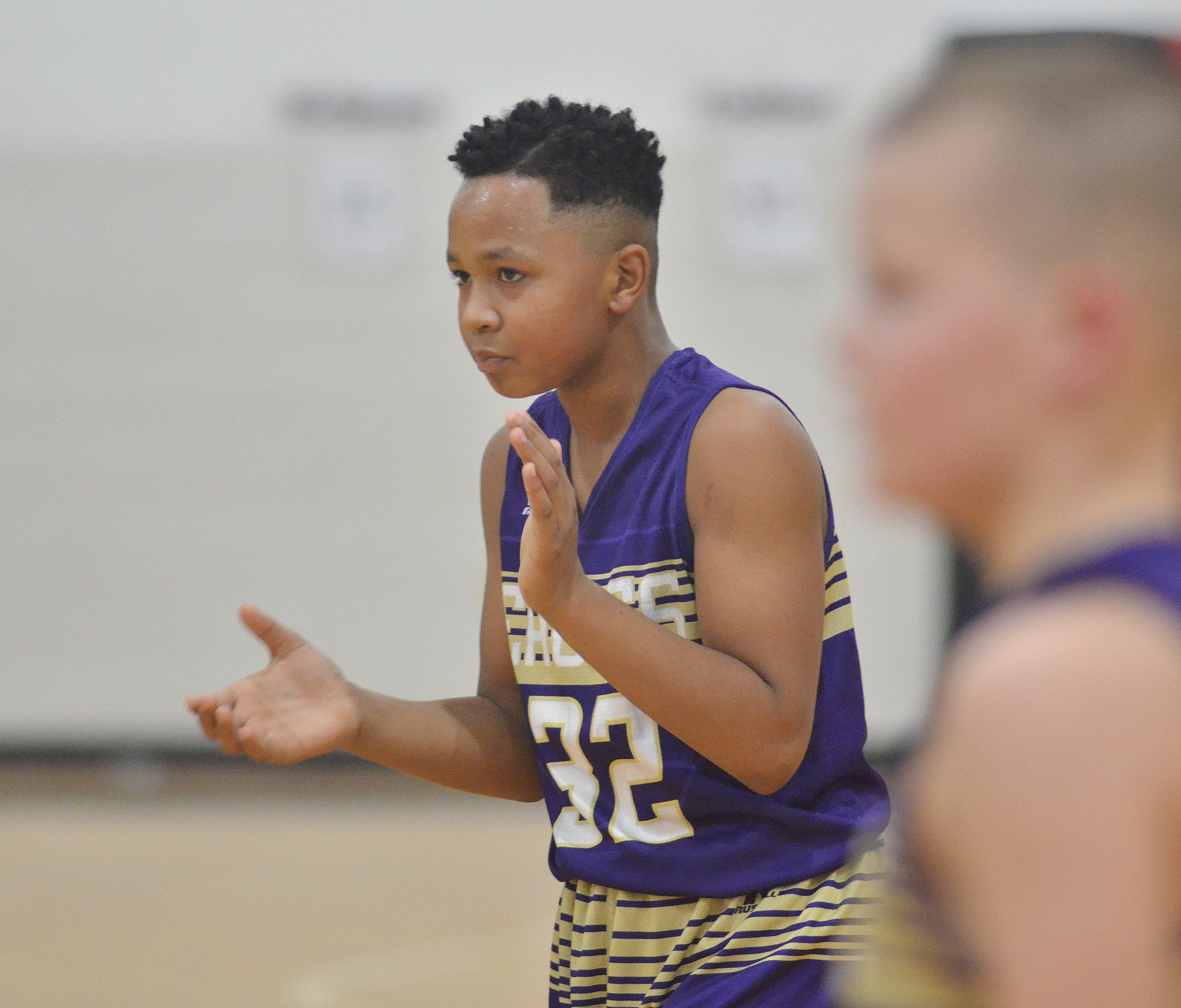 CMS sixth-grader Deondre Weathers clasps as his team scores.