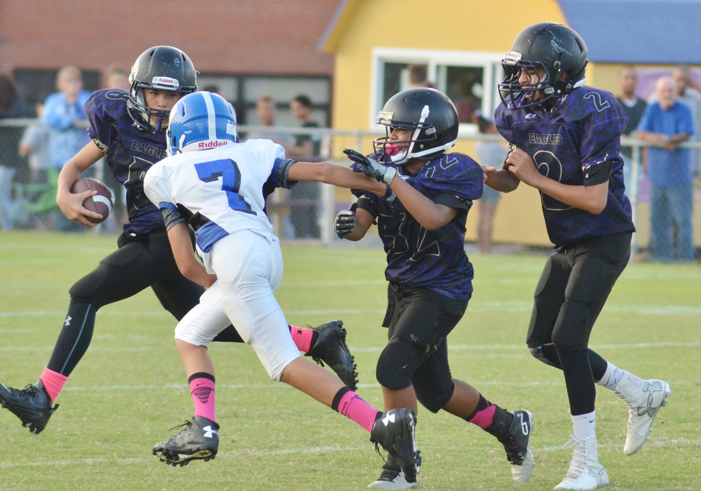 CMS sixth-grader Gavin Oliver runs the ball as teammates Deondre' Weathers, also a sixth-grader, and seventh-grader Adrien Smith, at right, block for him.