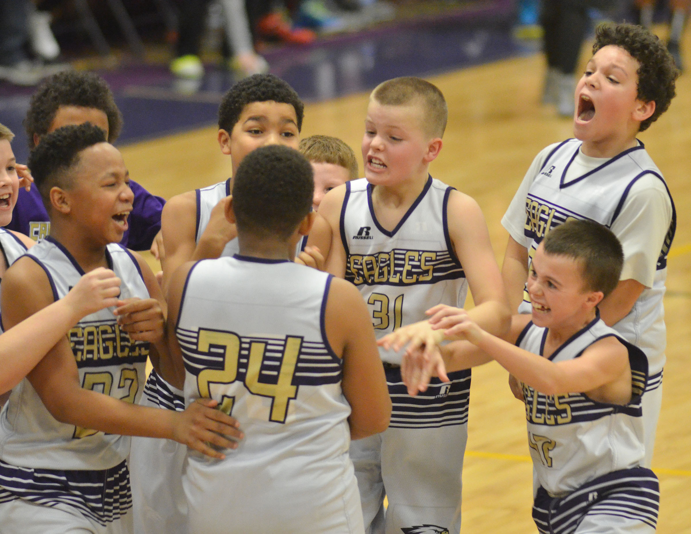 CMS sixth-grade players celebrate after Keondre Weathers, center, makes a foul shot to win the ball game.
