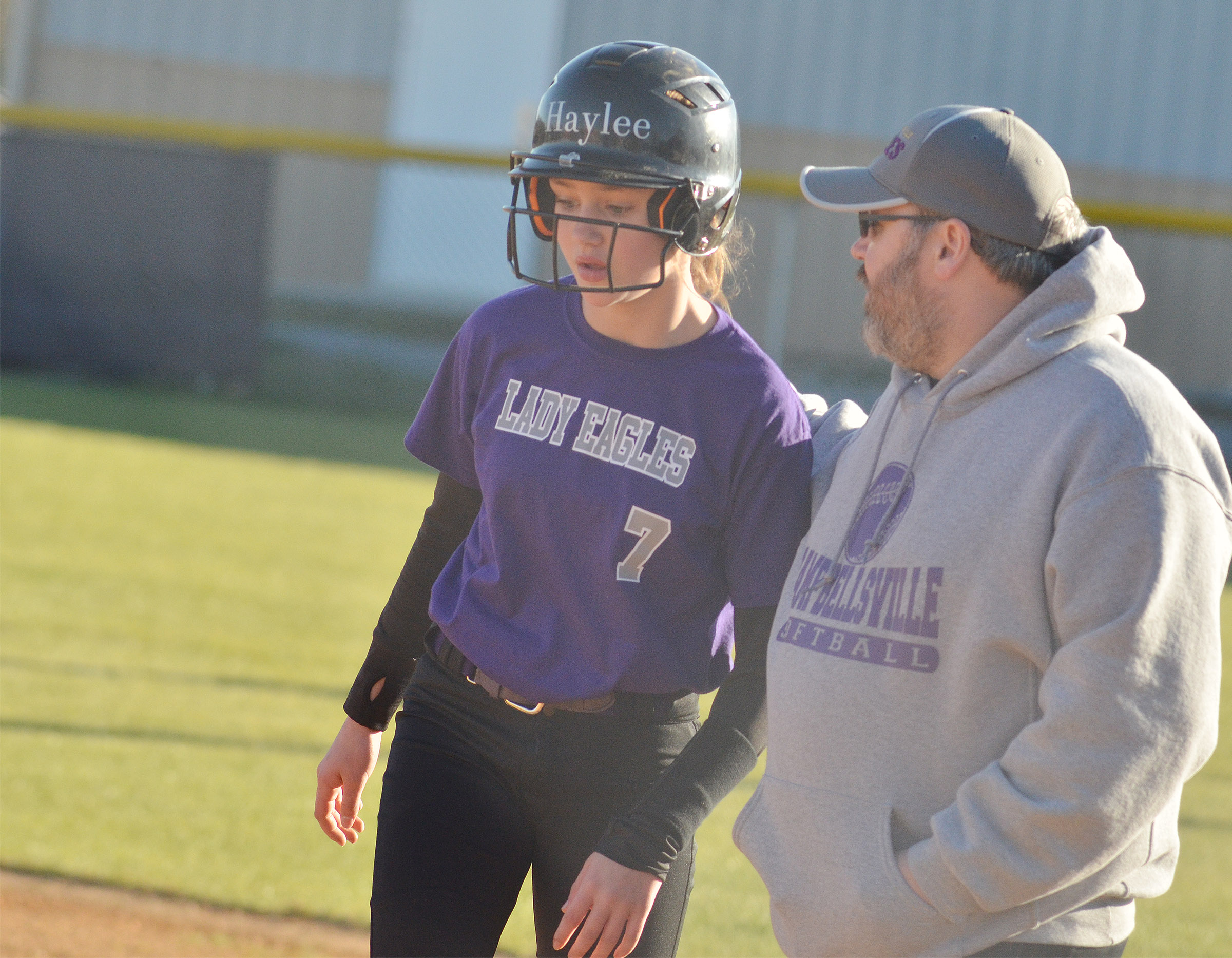 CMS sixth-grader Haylee Allen talks to assistant coach Joey Fields after she makes it to first.