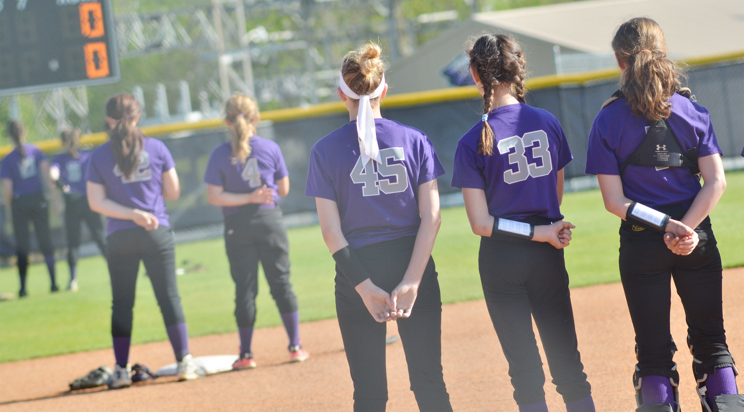 CMS softball players stand for the National Anthem.