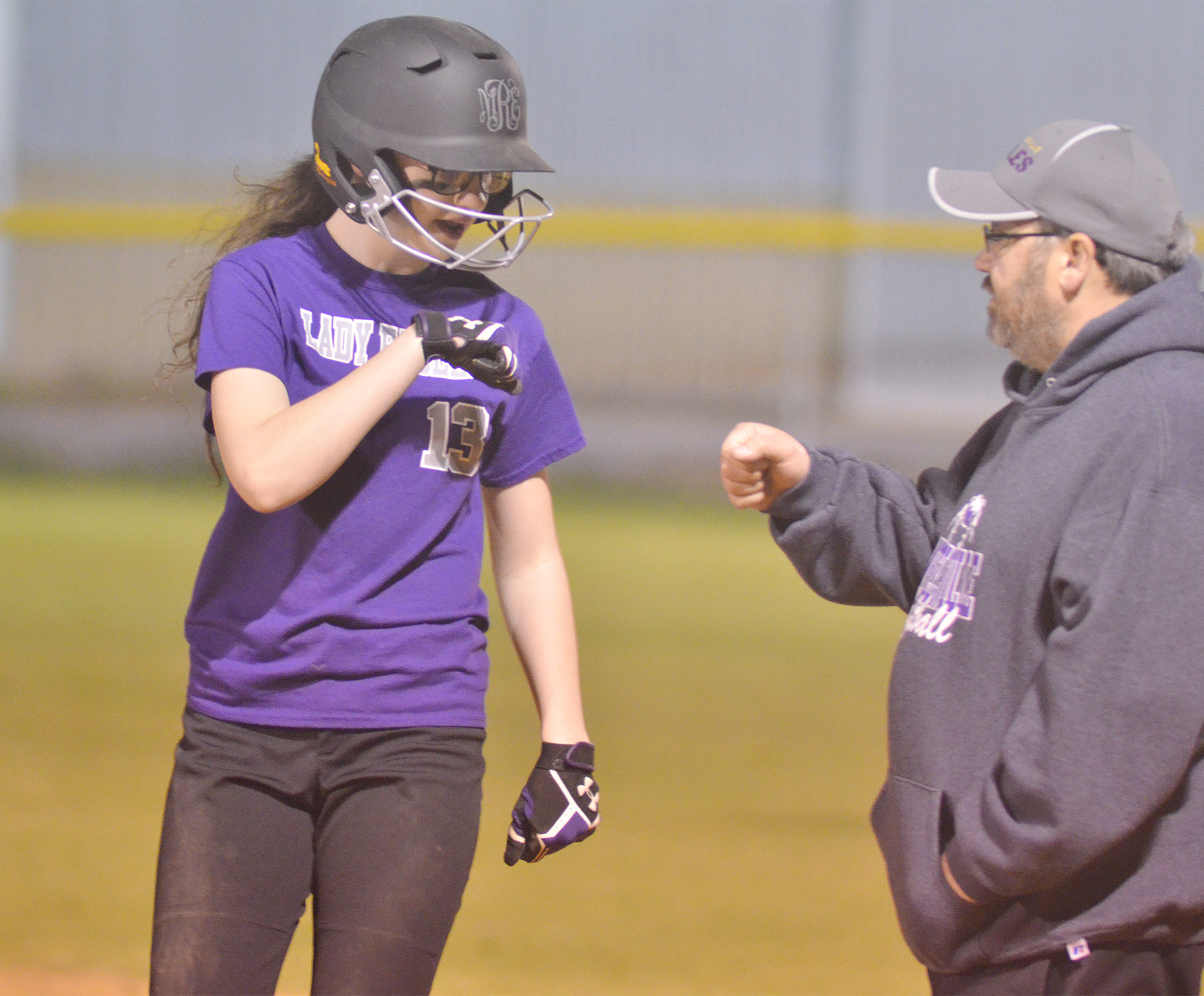 CMS sixth-grader Mary Russell bumps fists with assistant coach Joey Fields after getting a hit.