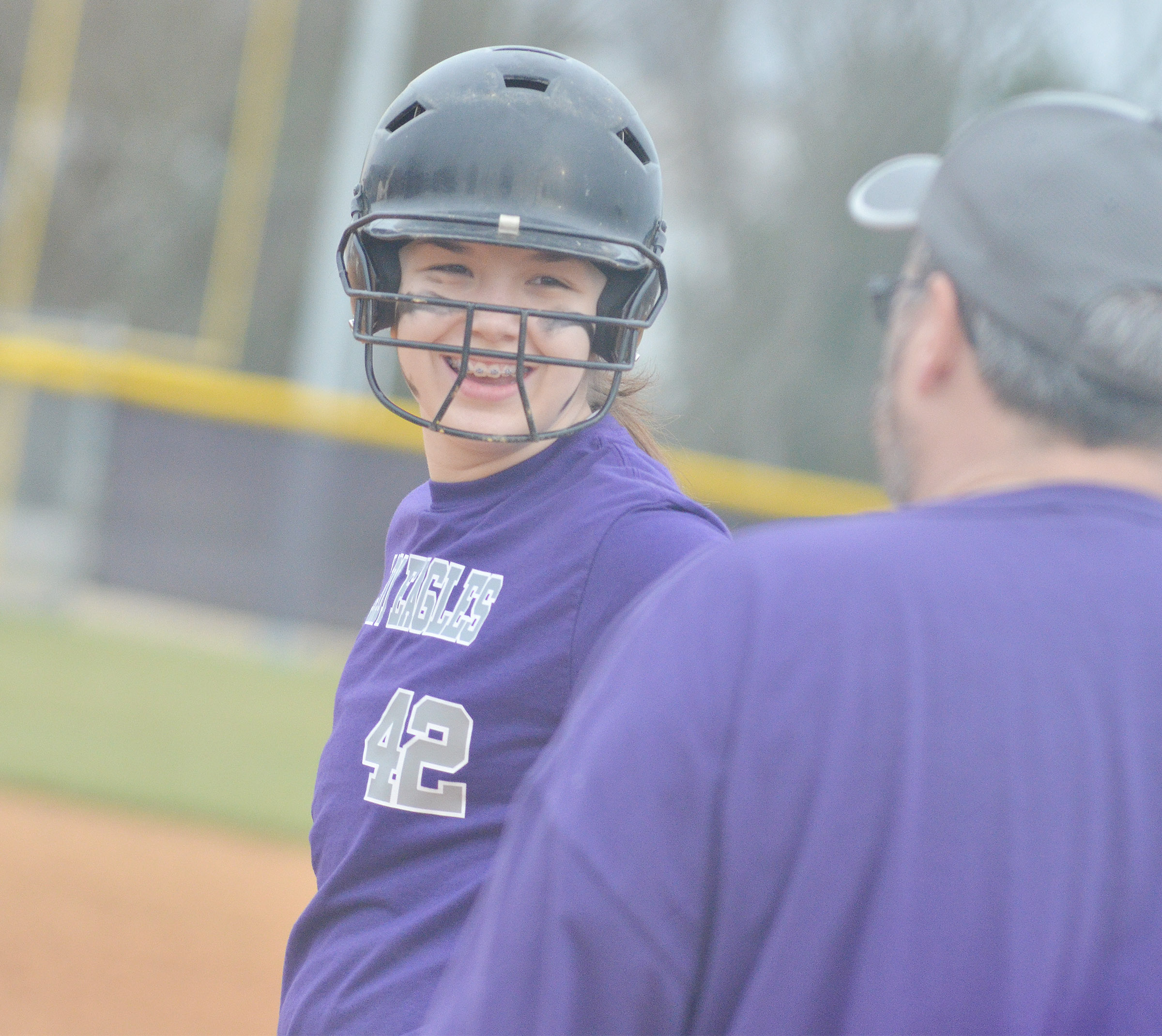 CMS seventh-grader Olivia Fields smiles as her dad, assistant coach Joey Fields, talks to her after a hit.