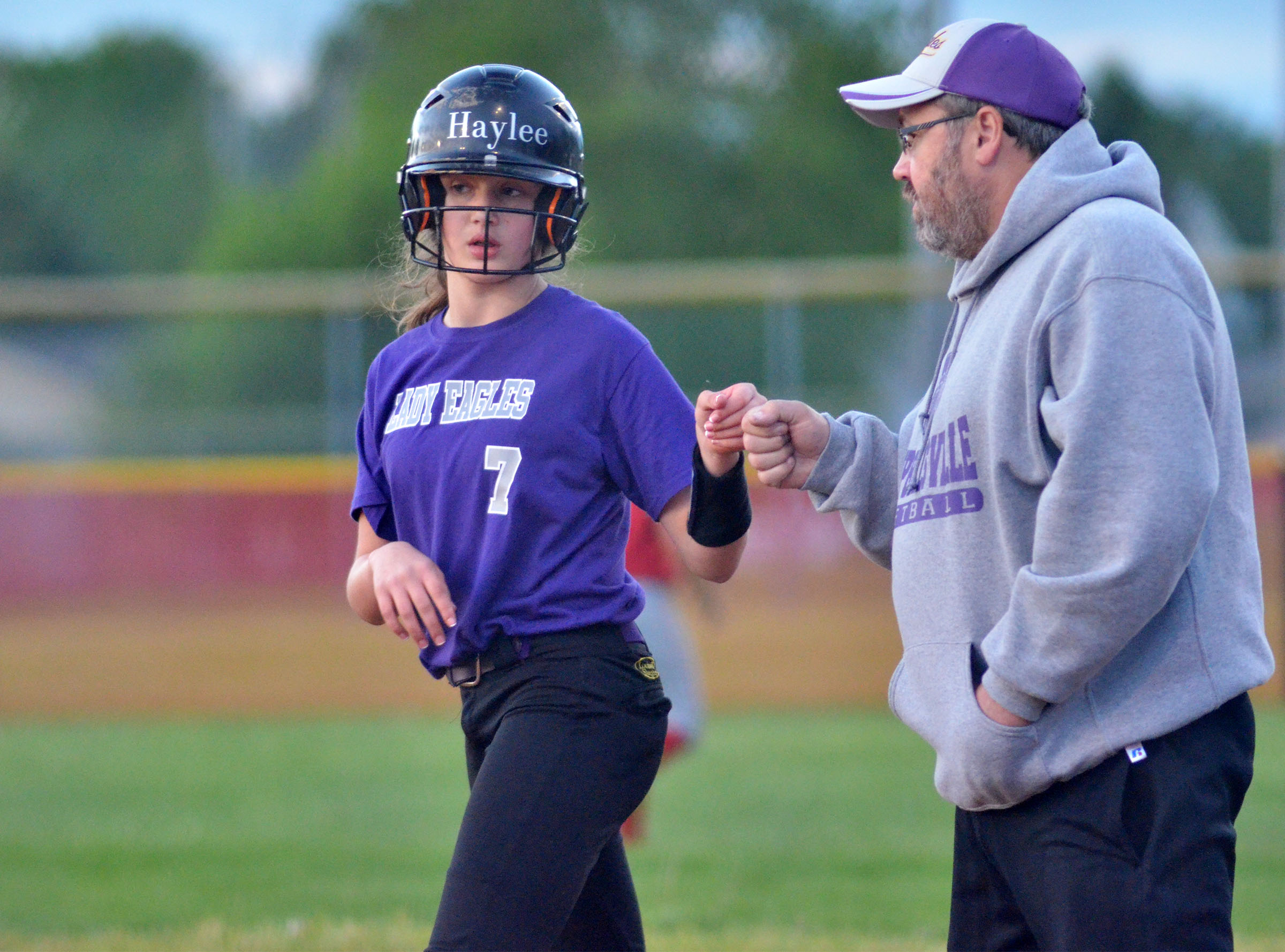 CMS sixth-grader Haylee Allen bumps fists with assistant coach Joey Fields after a hit.