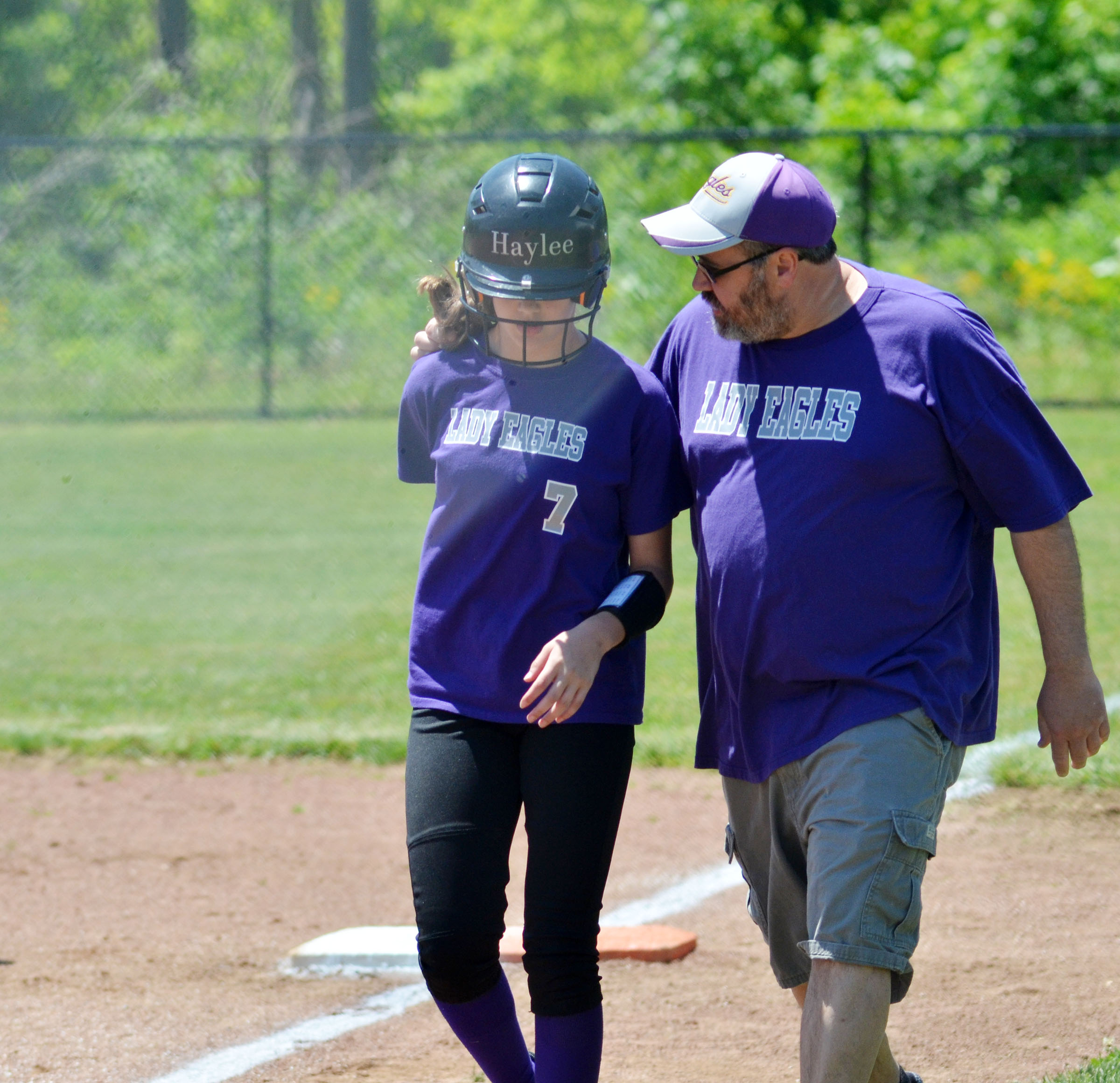 CMS assistant coach Joey Fields talks to sixth-grader Haylee Allen as they walk to the dugout.