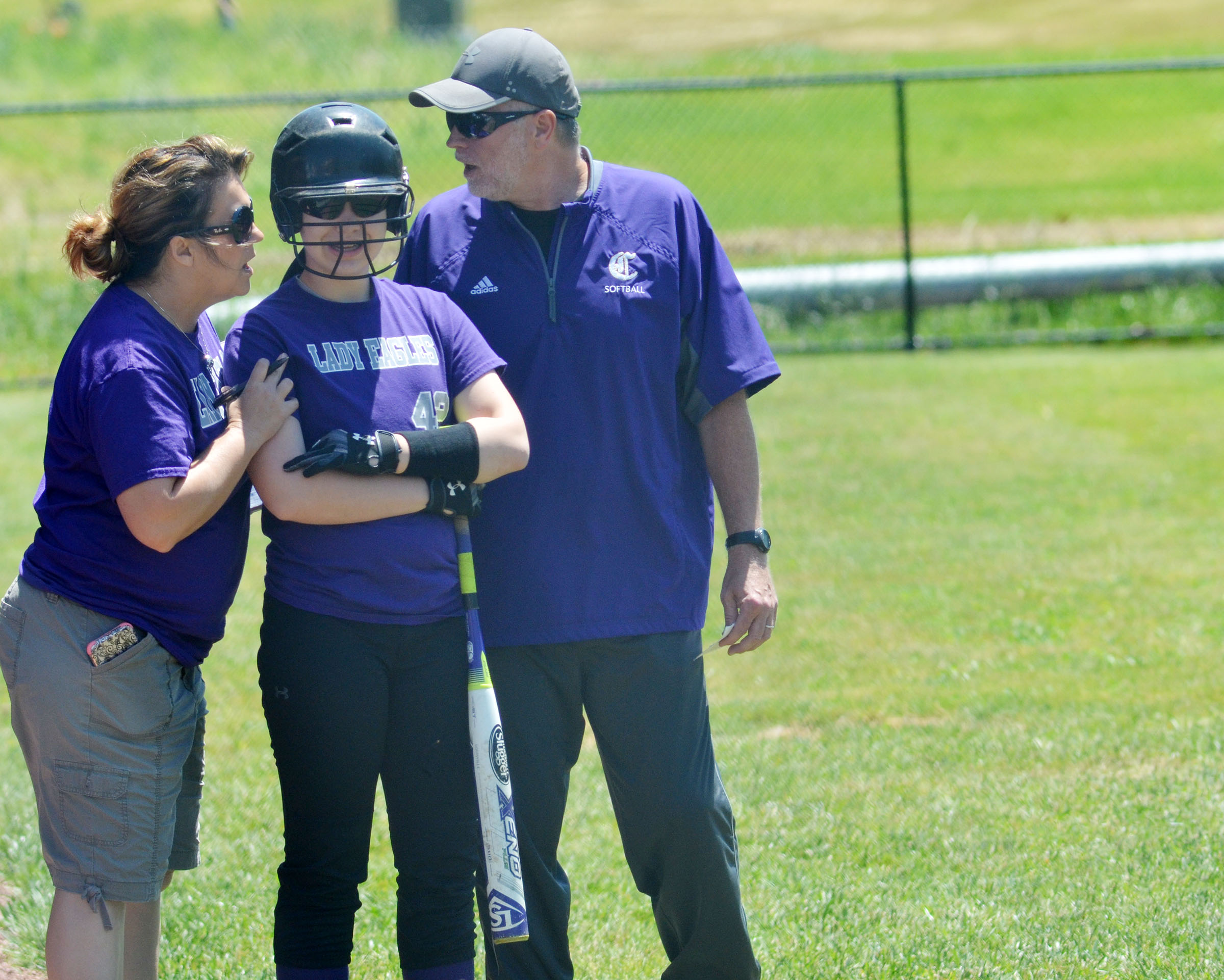 CMS head coach Kathy England, at left, and assistant coach Bobby Hayes talk to seventh-grader Olivia Fields as she gets to set to bat.
