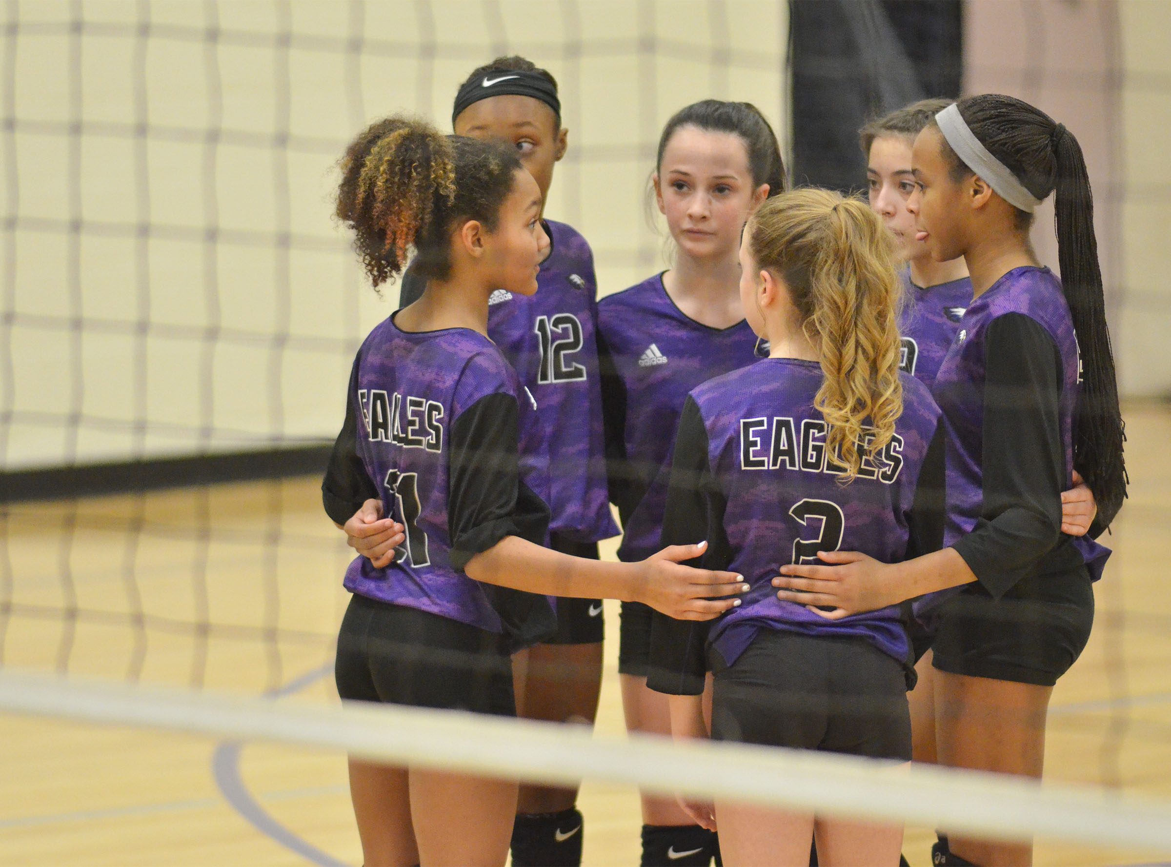 CMS volleyball players talk before a play.