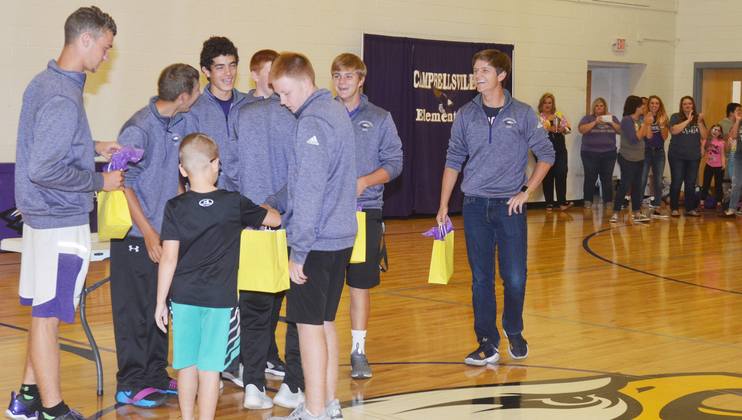 CHS golf players receive treat bags from Campbellsville Elementary School fourth-grader Cameron Estes.