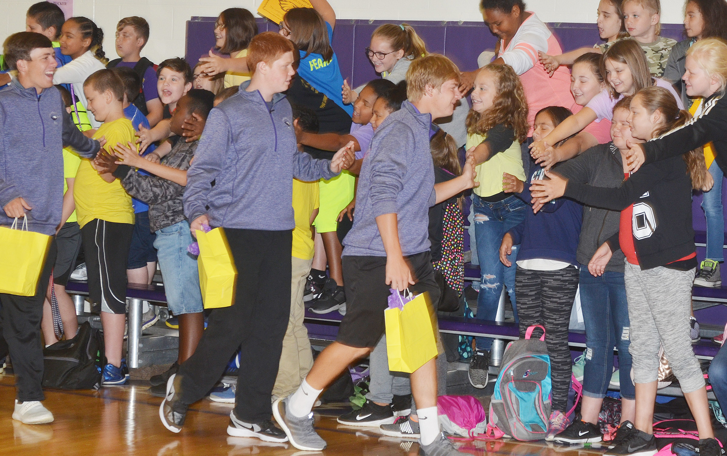 CHS golf players, from left, junior Layton Hord, freshman Colin Harris and senior Alex Doss high-five CES students.