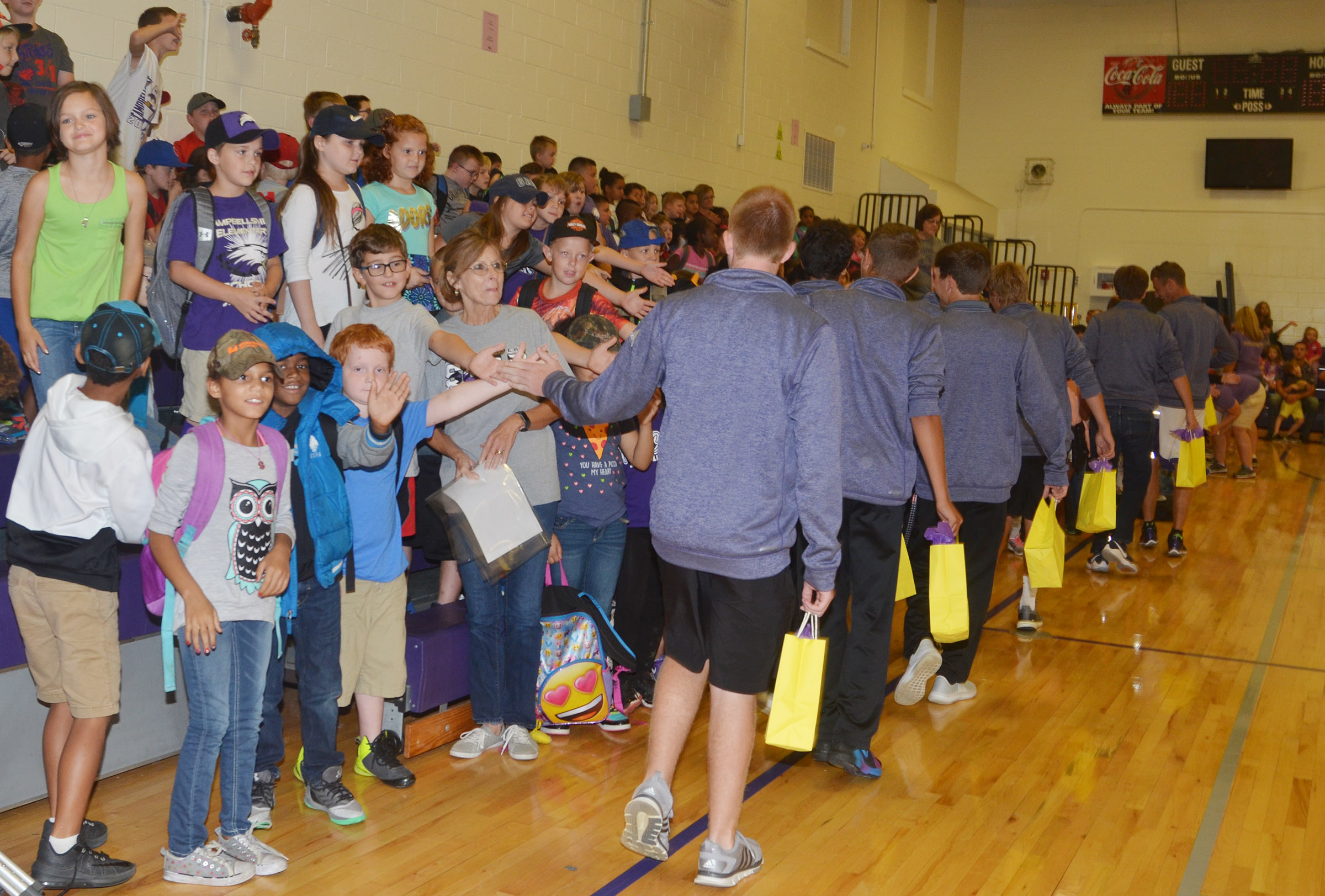 CHS golf players high-five CES students.