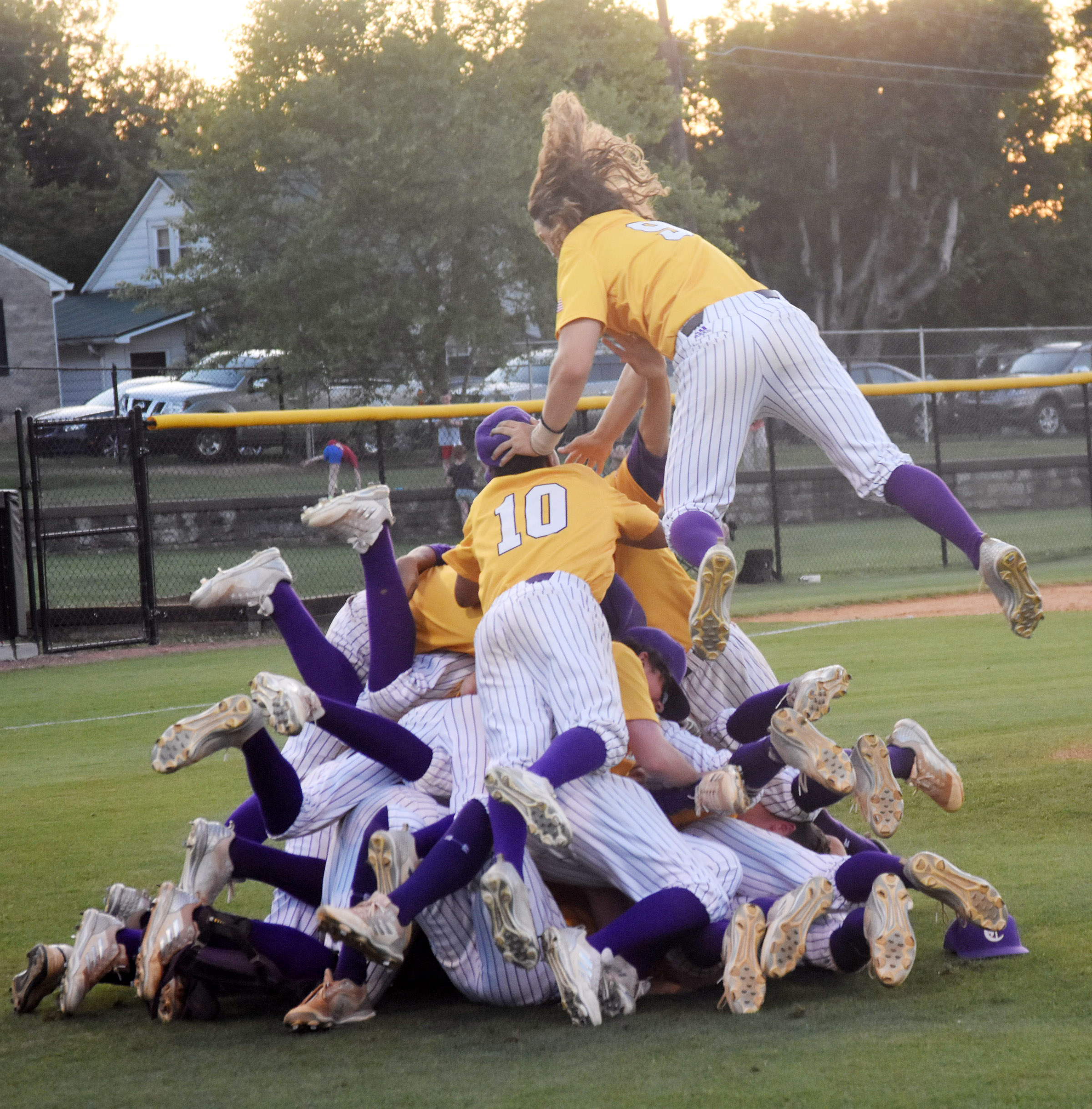 CHS junior Treyce Mattingly jumps atop a pile of players after his team wins the 20th District championship.