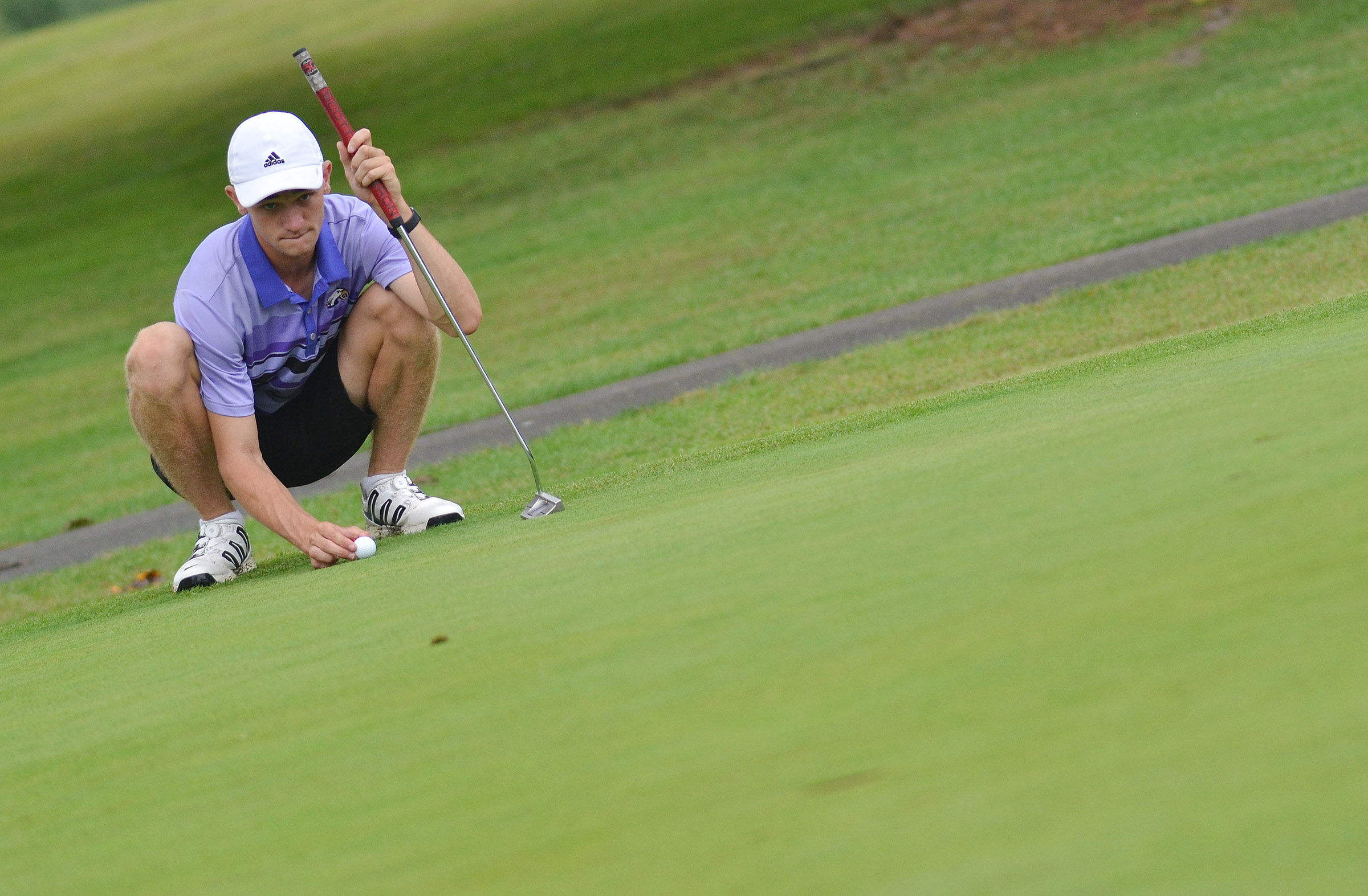 CHS senior Connor Wilson lines up his putt.