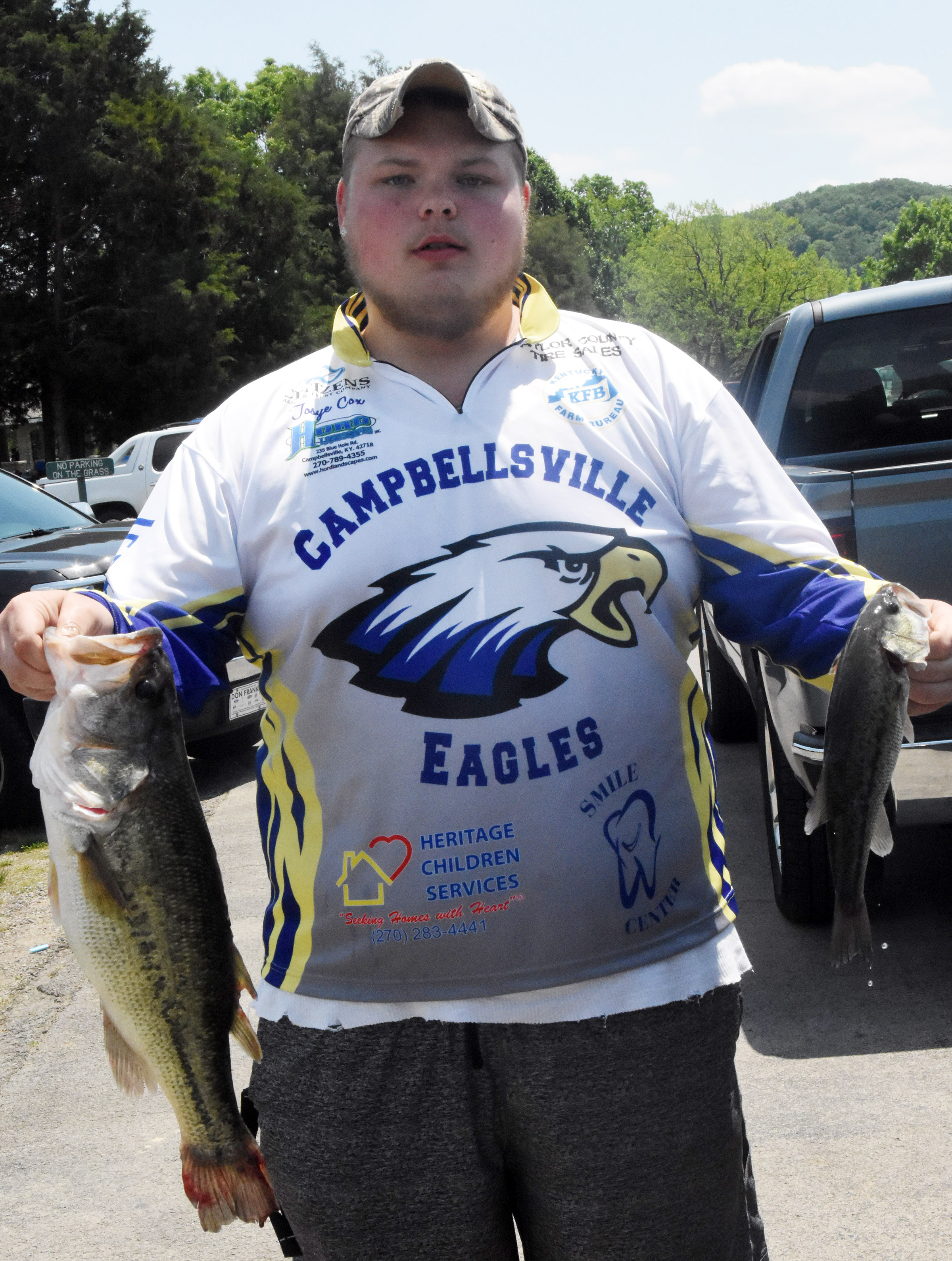 CHS senior Tosye Cox holds his and classmate Caleb Hughes's fish, which were big enough to earn them the CHS Bass Fishing Tournament champion title.