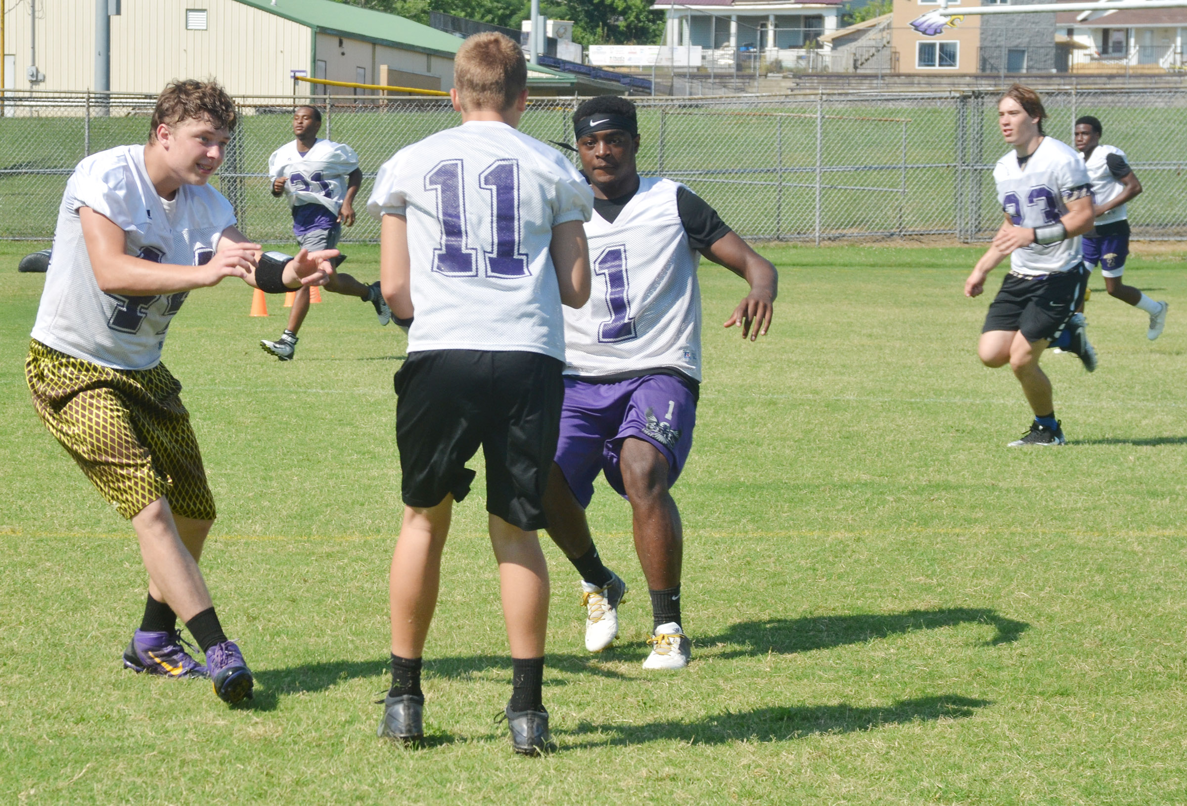CHS sophomore Devon Reardon, at left, and junior Charlie Pettigrew tackle sophomore Tyler Gribbins as he runs the ball.