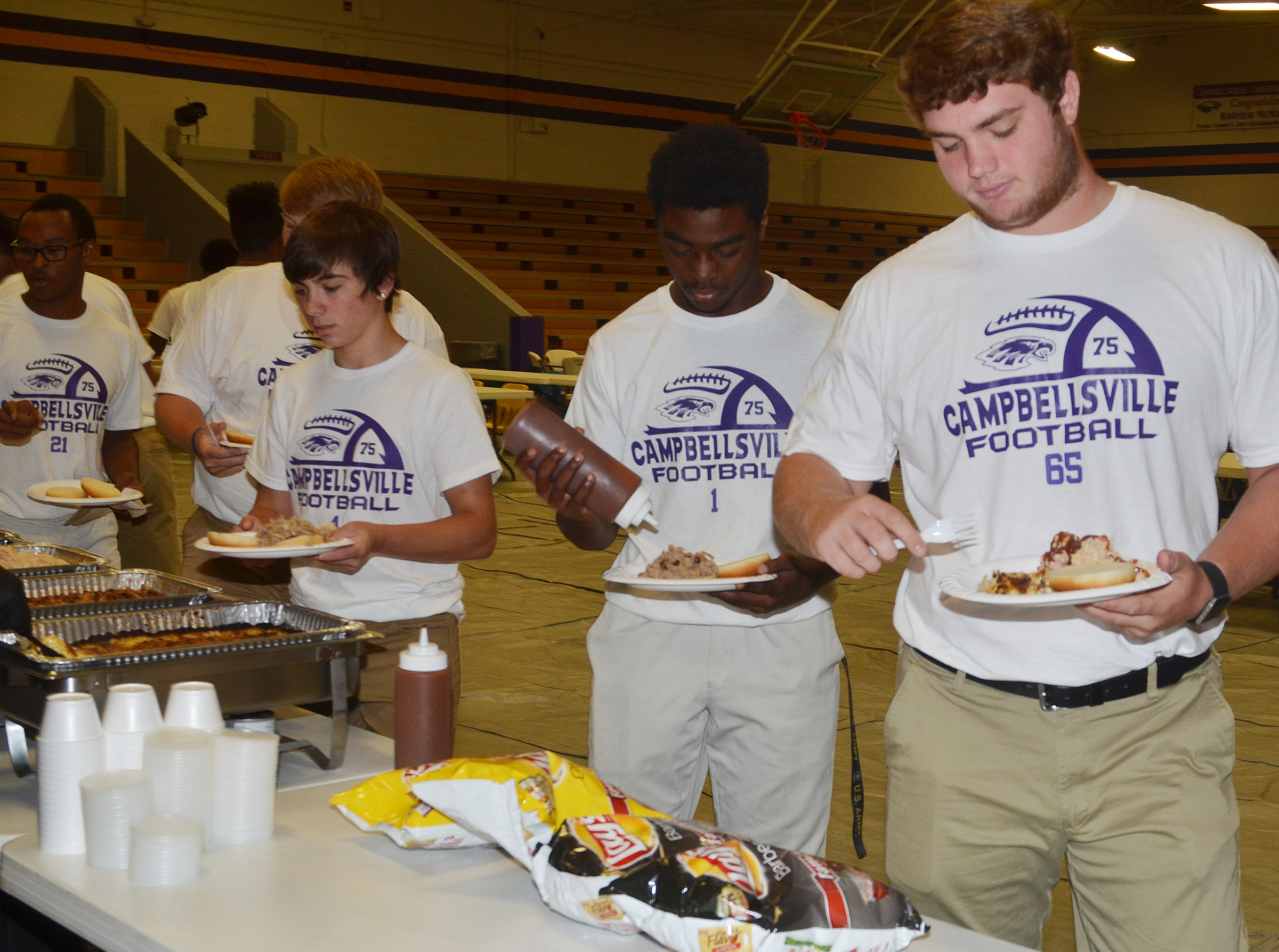 CHS junior Lane Bottoms, at right, and his teammates eat at the annual CHS football dinner and auction.