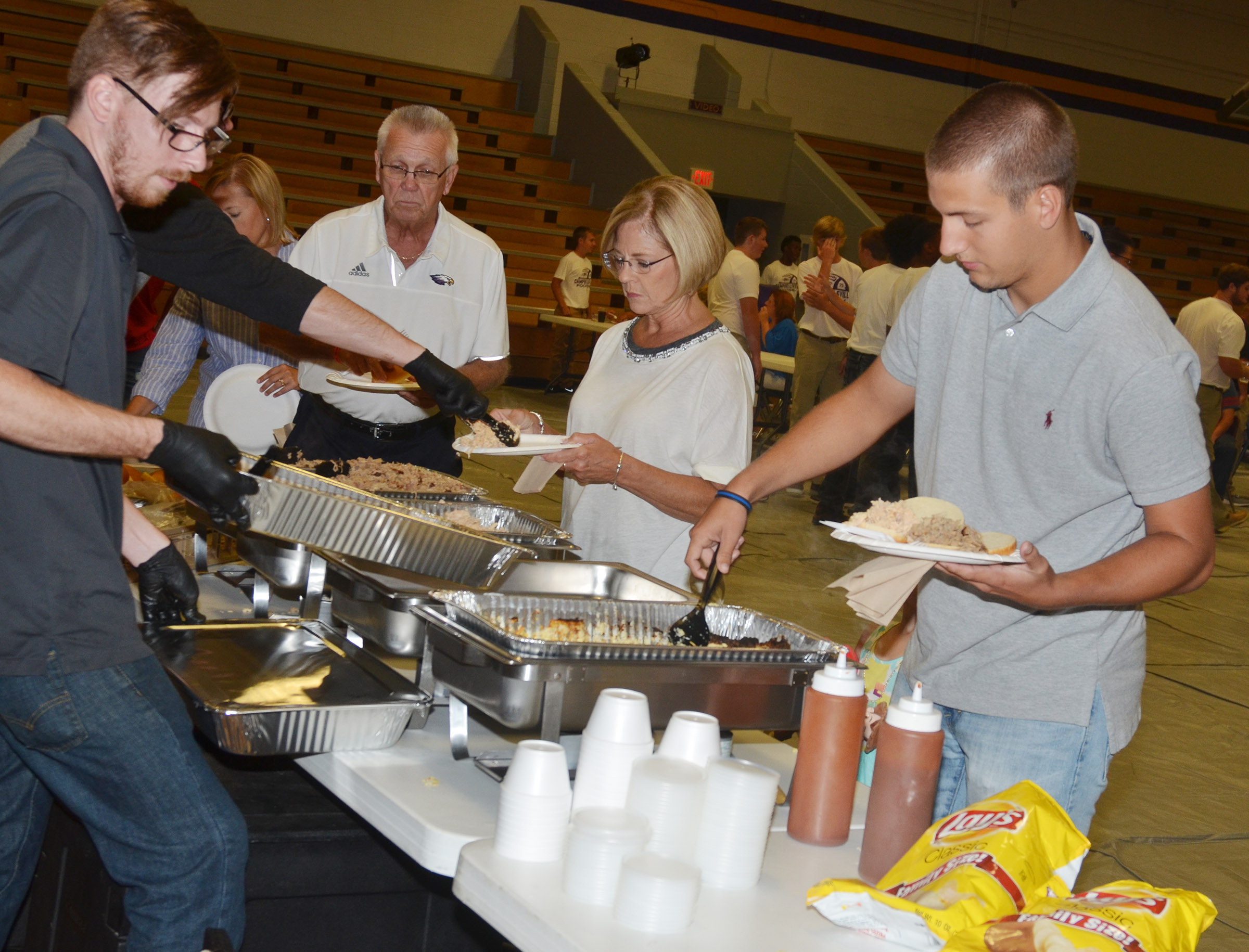 From left, Kelly and Debbie Baugh and Zach Durham, an instructional assistant at Campbellsville Elementary School, are served at the annual CHS football dinner and auction.