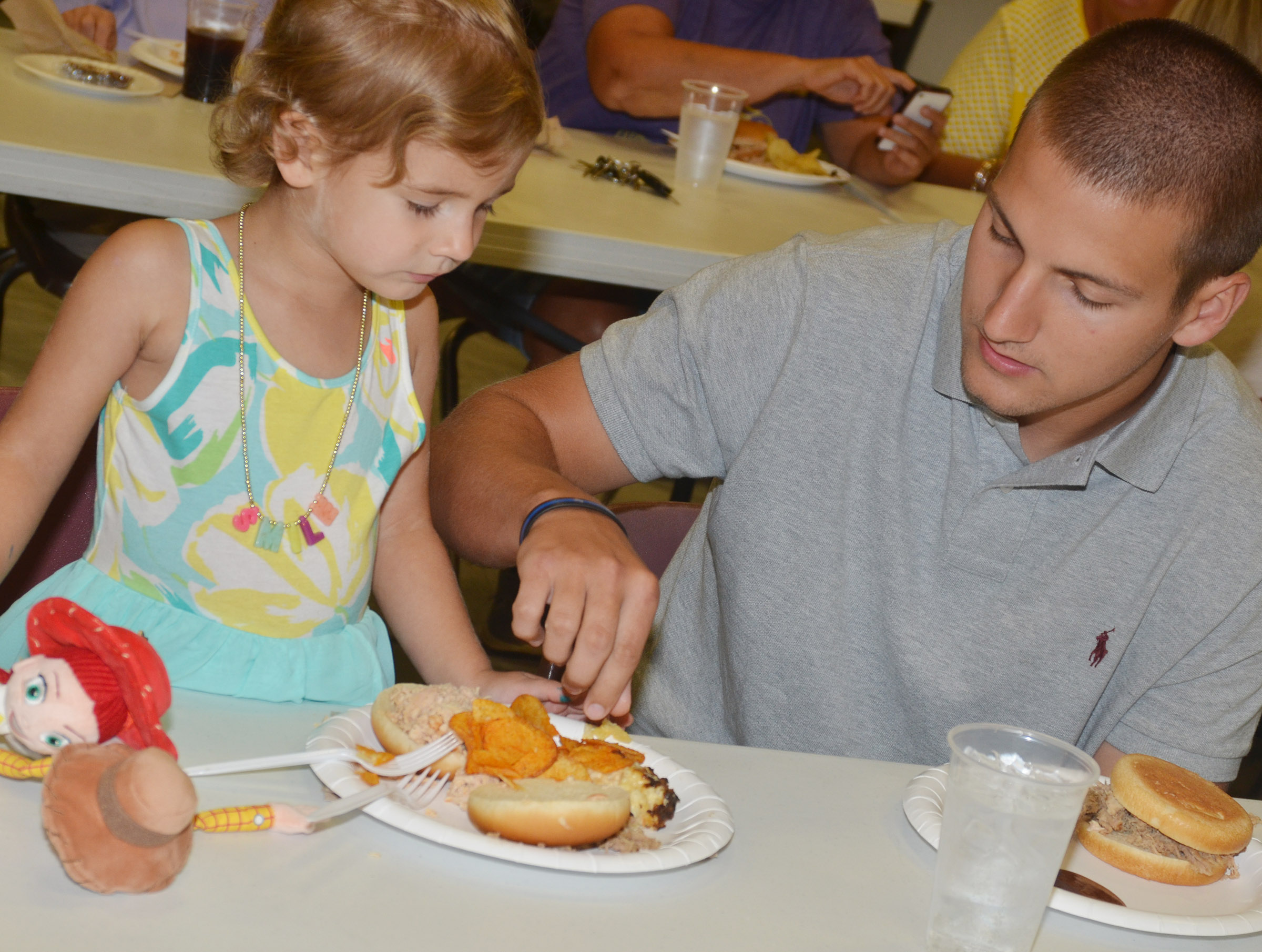 Zach Durham, an instructional assistant at Campbellsville Elementary School, helps his daughter, Chandler, eat her lunch at the annual CHS football dinner and auction.