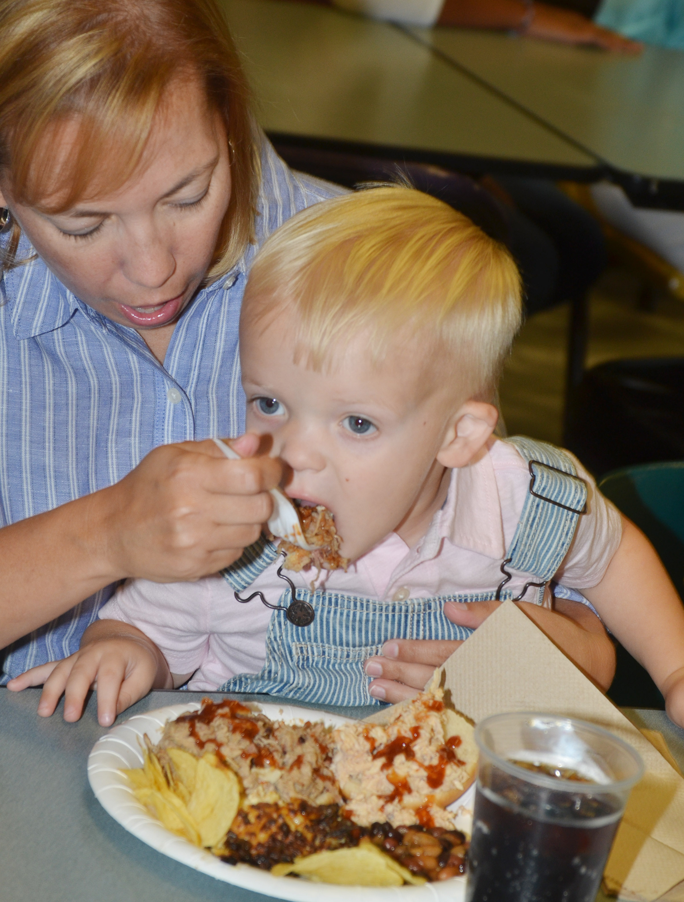Erin Estes helps her son, Cooper, eat a bite of barbecue at the annual CHS football dinner and auction. Estes is married to Dale Estes, the head football coach at CHS.