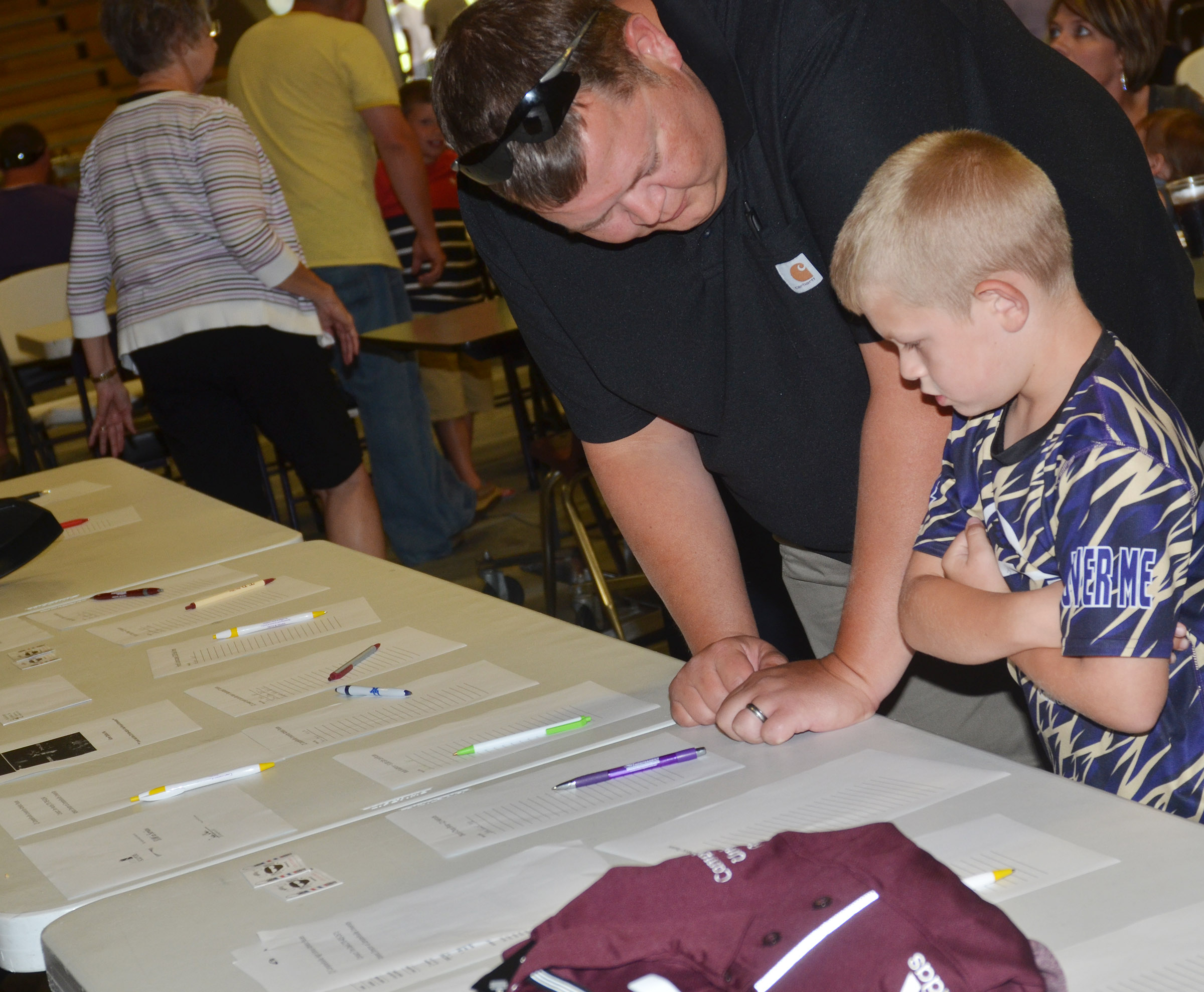 Steven Thomas and his son, Grif, check out the auction items at the annual CHS football dinner and auction.