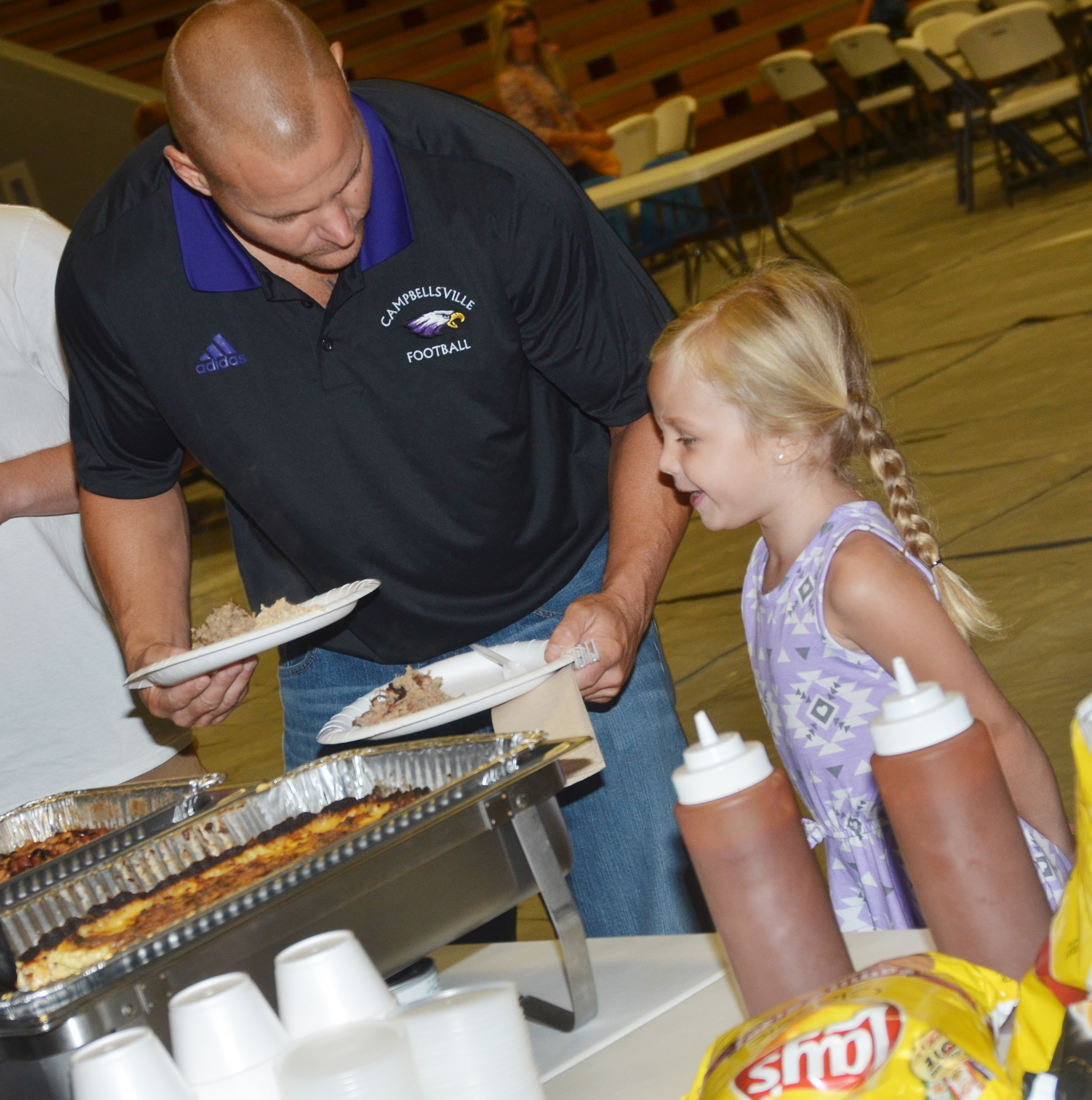 CHS assistant football coach Robbie Gribbins helps his daughter, Trinidy, a kindergartener at Campbellsville Elementary School, get some barbecue for lunch.