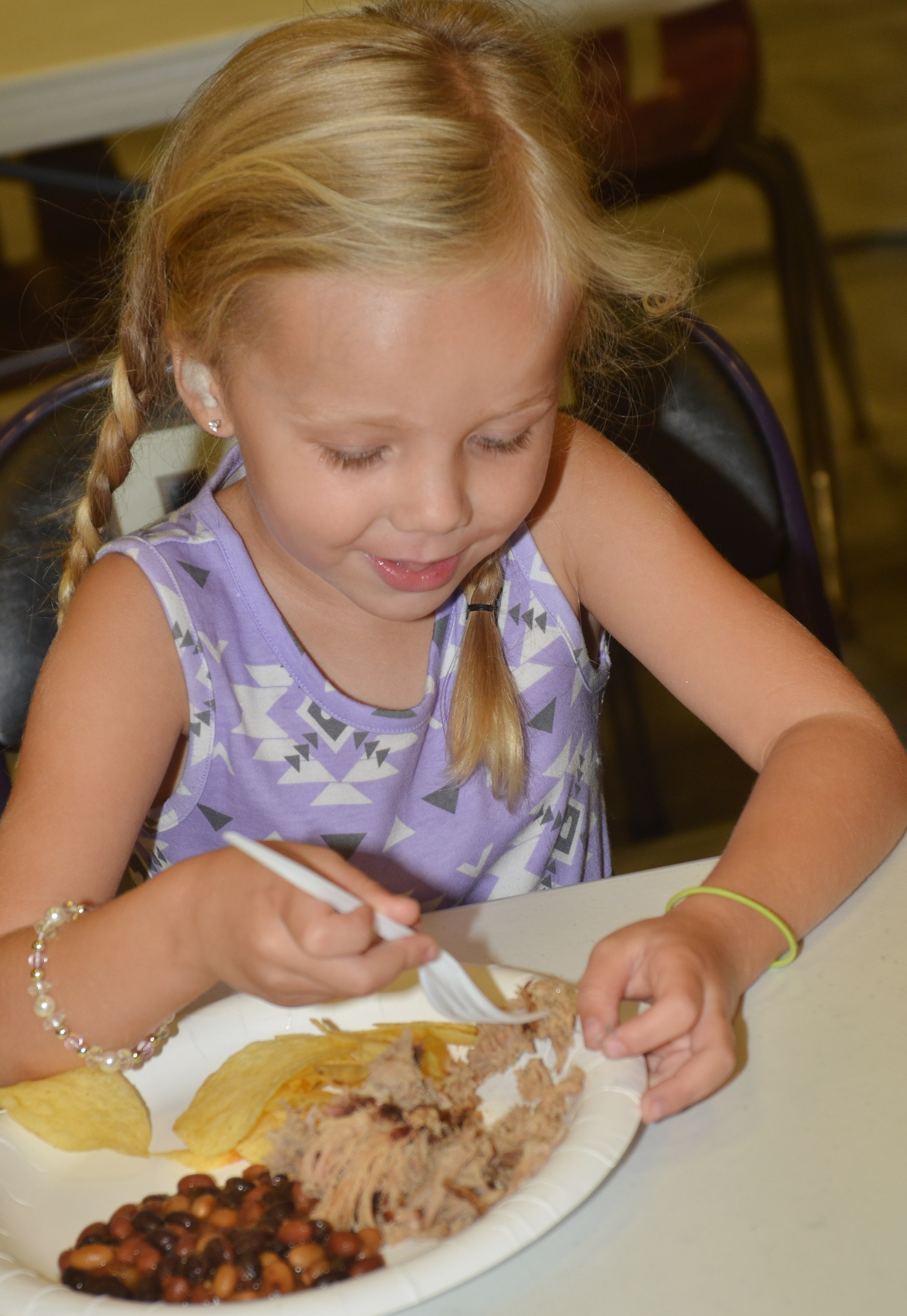 Campbellsville Elementary School kindergartener Trinidy Gribbins eats at the annual CHS football dinner and auction.
