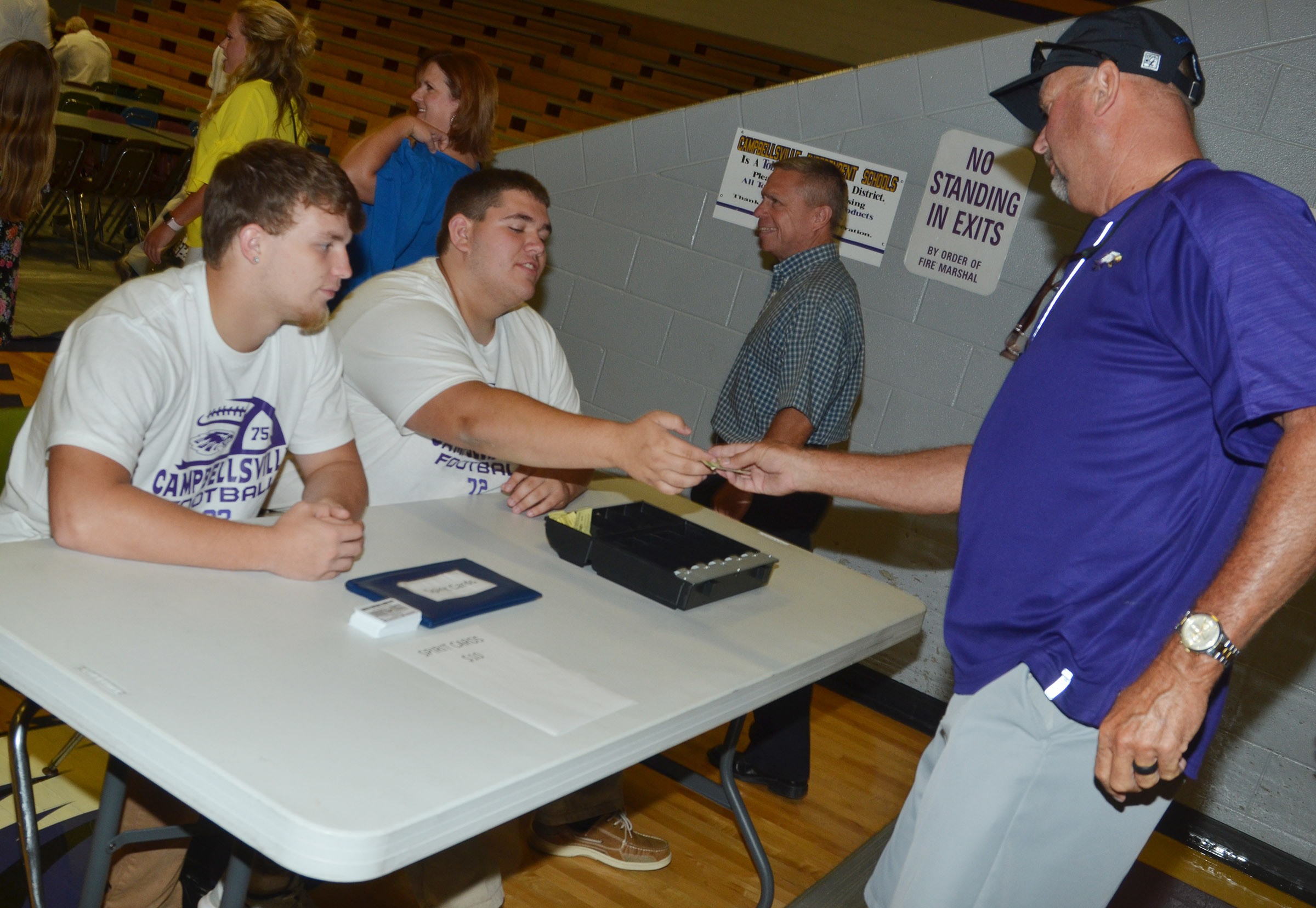 CHS junior Dakota Reardon, at left, and senior Ryan Wiedewitsch sell a dinner ticket to CHS Athletic Director Tim Davis.