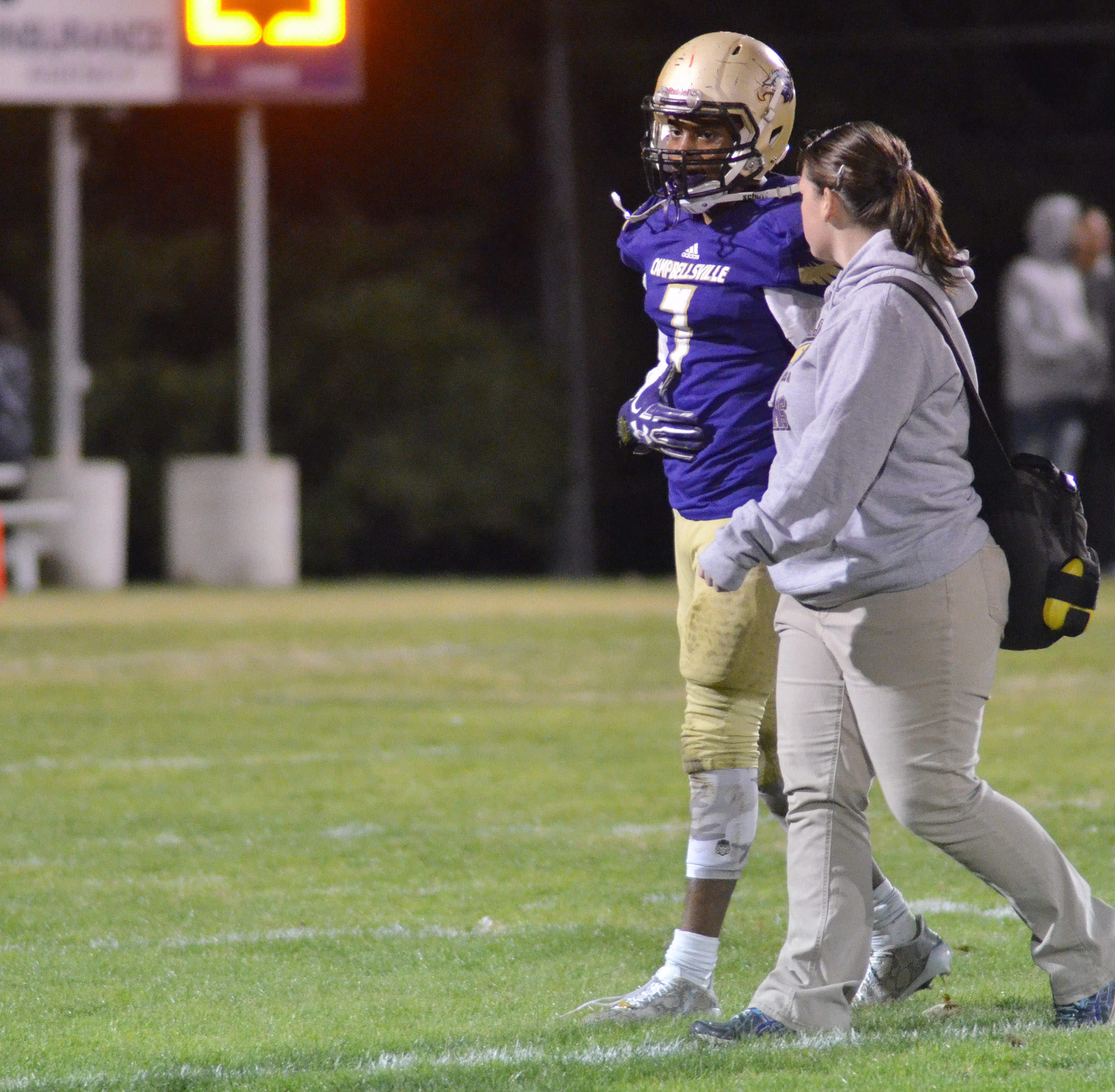 CHS senior Devonte Cubit walks off the field with trainer Rebecca Cravens.