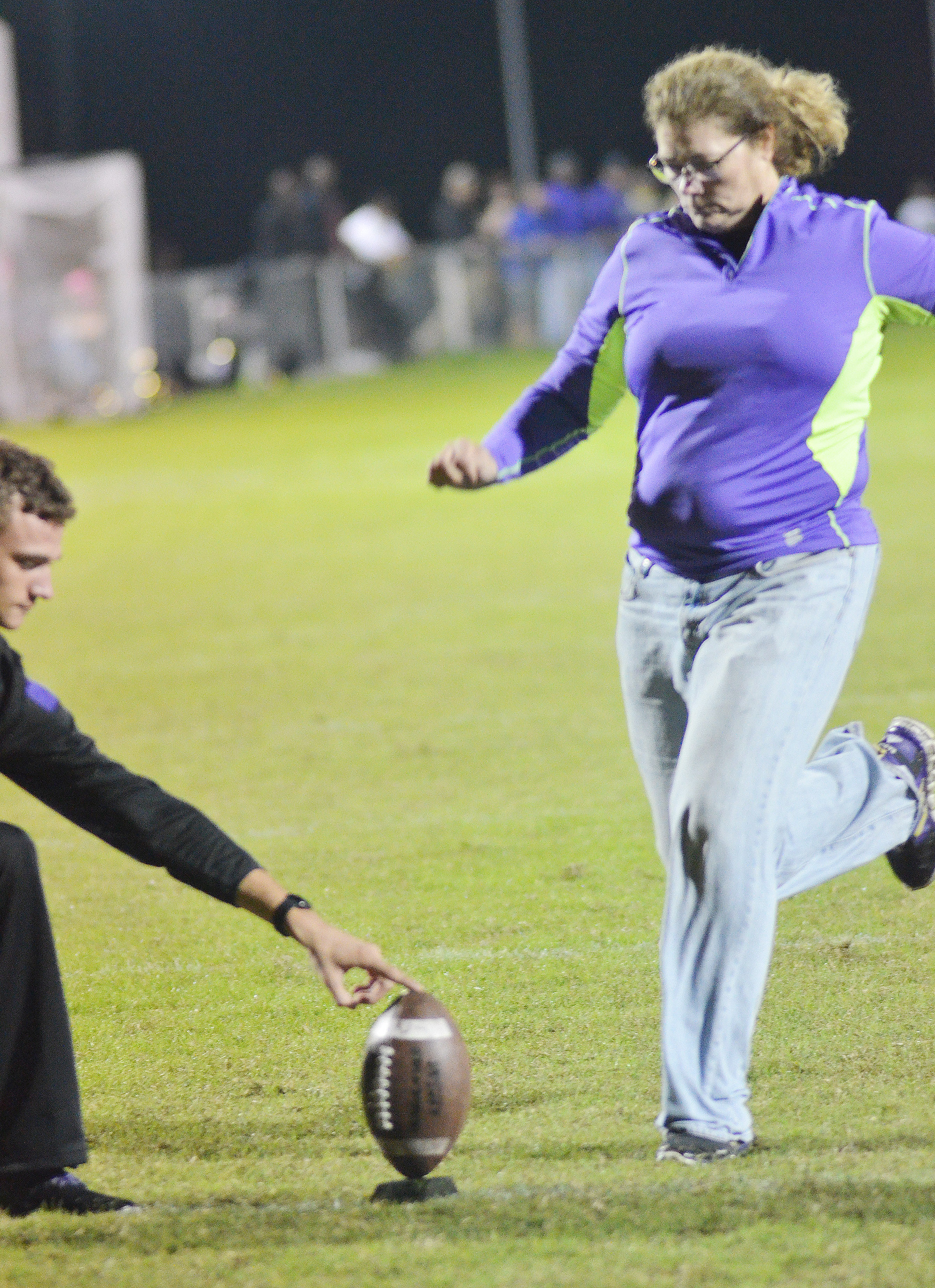 CHS teacher Tammy Wilson kicks a field goal to win senior Austin Fitzgerald a $50 prize in the Kick for Kids, sponsored by Kentucky Farm Bureau.